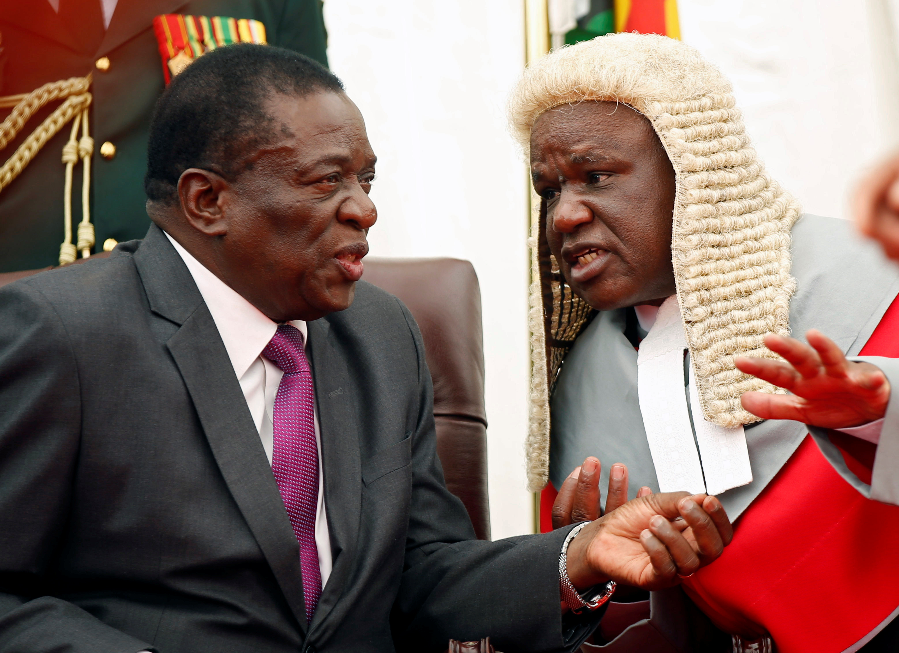 Zimbabwean President Emmerson Mnangagwa talks to the Chief Justice Luke Malaba during the swearing in ceremony of the country's vice presidents at State House in Harare, Zimbabwe, December 28,2017.REUTERS/Philimon Bulawayo