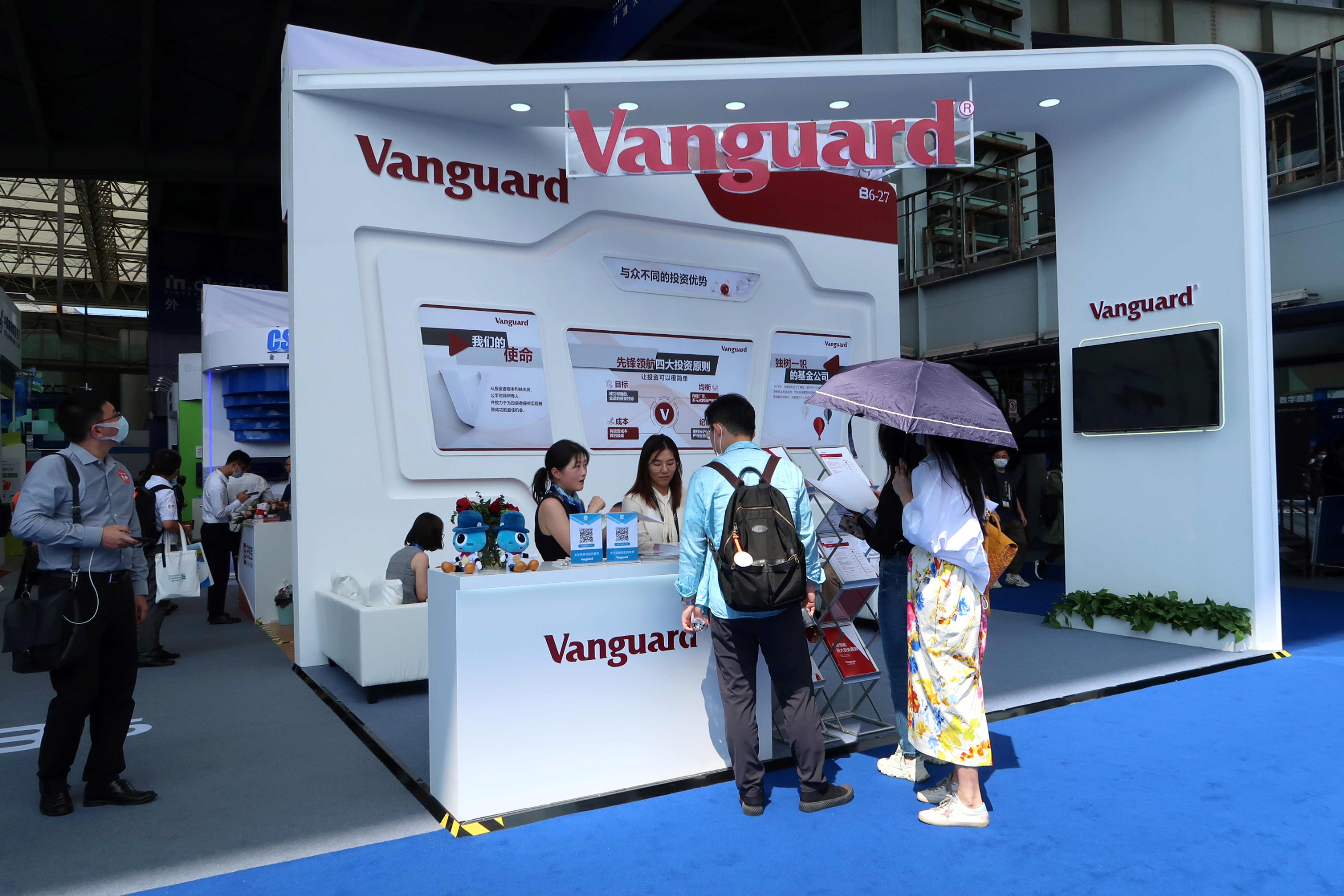 People are seen at a booth of Vanguard Group at a fair during the INCLUSION fintech conference in Shanghai, China September 24, 2020. REUTERS/Cheng Leng