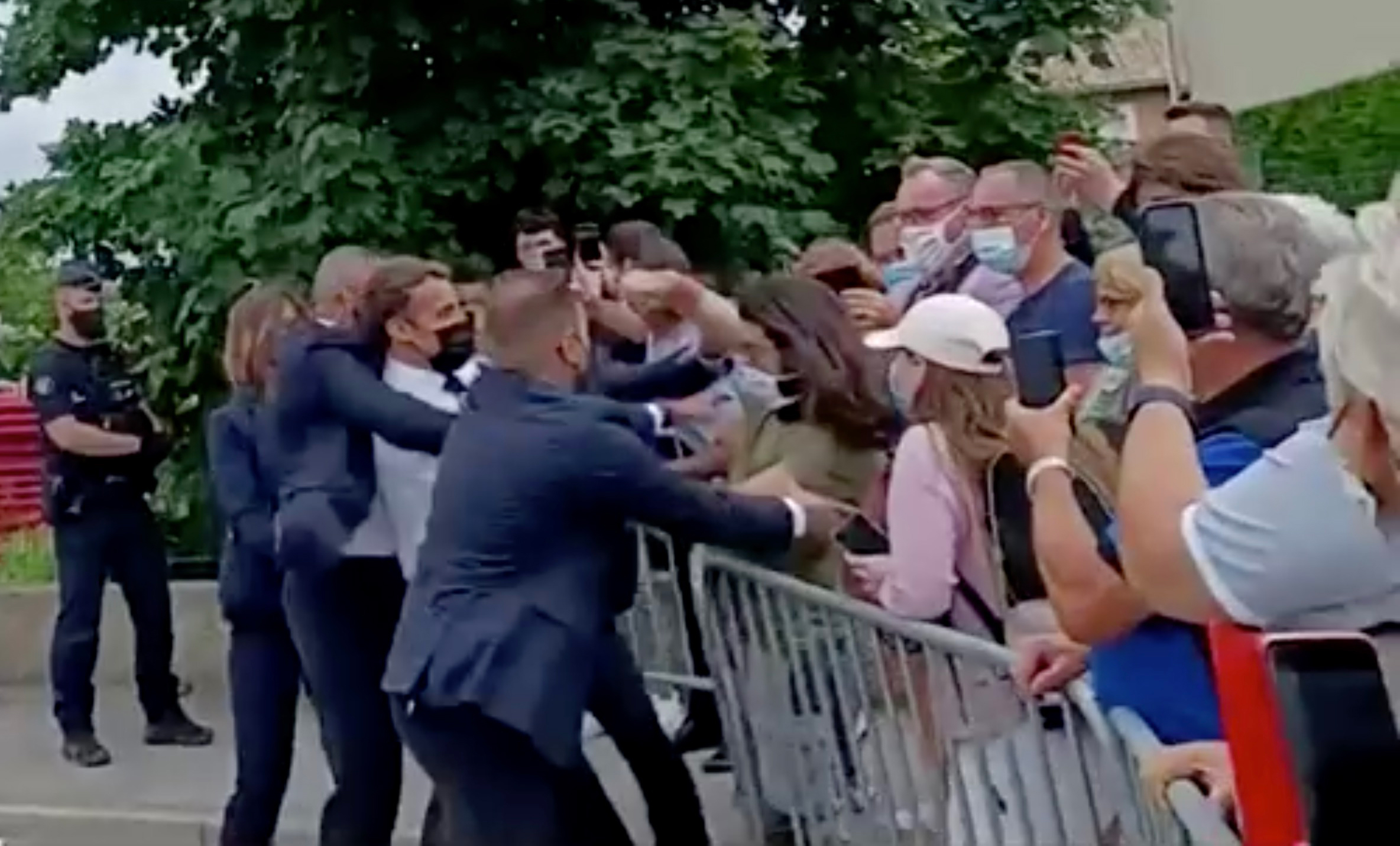 French President Emmanuel Macron is slapped in the face by a member of the public during a visit to Tain-l'Hermitage, France, June 8, 2021. BFMTV via Reuters TV