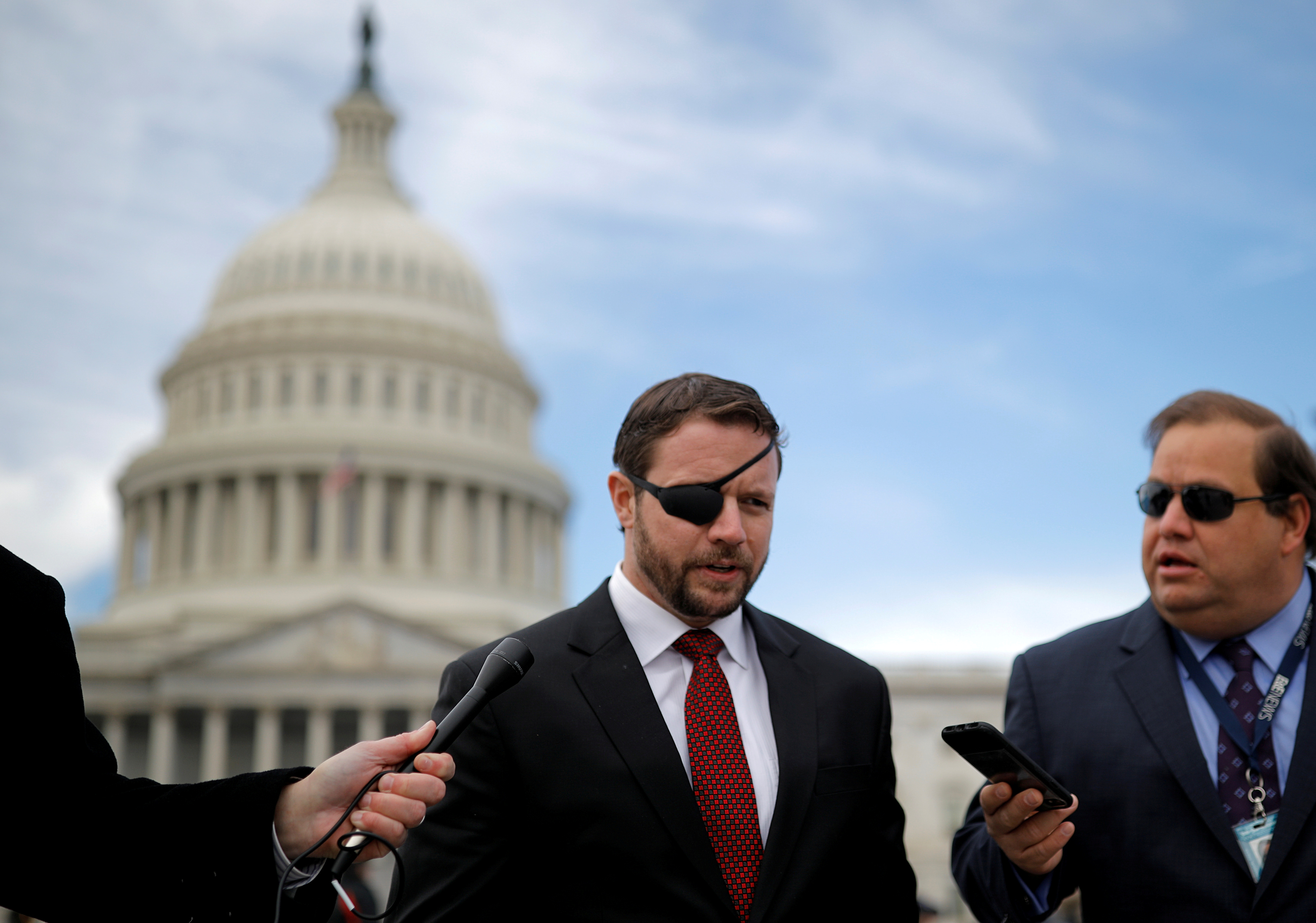 Republican Representative-elect Dan Crenshaw talks with reporters as he arrives for a class photo with incoming newly elected members of the U.S. House of Representatives on Capitol Hill in Washington, U.S., November 14, 2018. REUTERS/Carlos Barria/File Photo