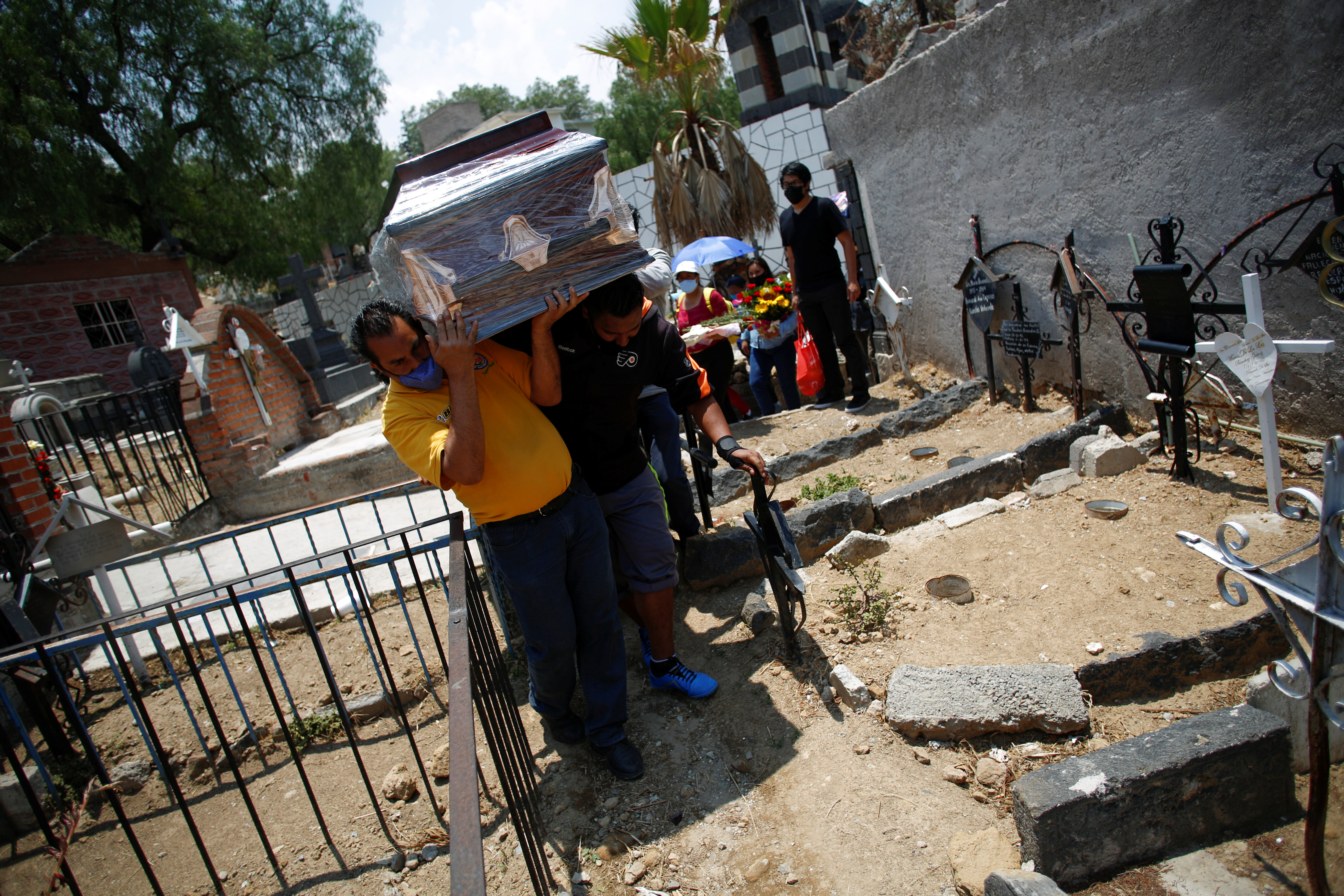 Relatives of late school teacher Karen Castillo, 35, who died from the coronavirus disease (COVID-19), carry her coffin while arriving for her funeral to a cemetery in Chimalhuacan, State of Mexico, Mexico May 18, 2021. Picture taken May 18, 2021. REUTERS/Gustavo Graf