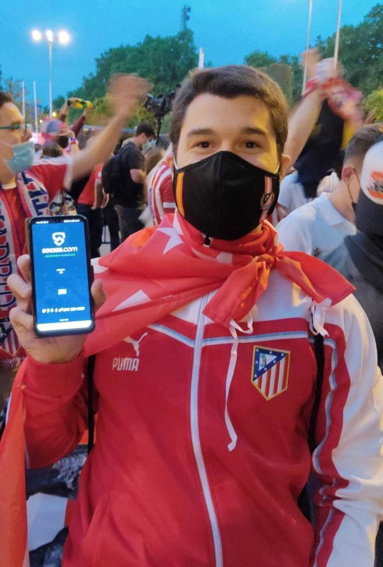 Alberto Diaz Arenas, a fan of Spain's Atletico Madrid soccer team, poses for a picture as he holds a phone with Chiliz's Socios.com app during the club's title celebrations in Madrid, Spain May 22, 2021 in this handout photo obtained by REUTERS on June 10, 2021. CHILIZ/Handout via REUTERS