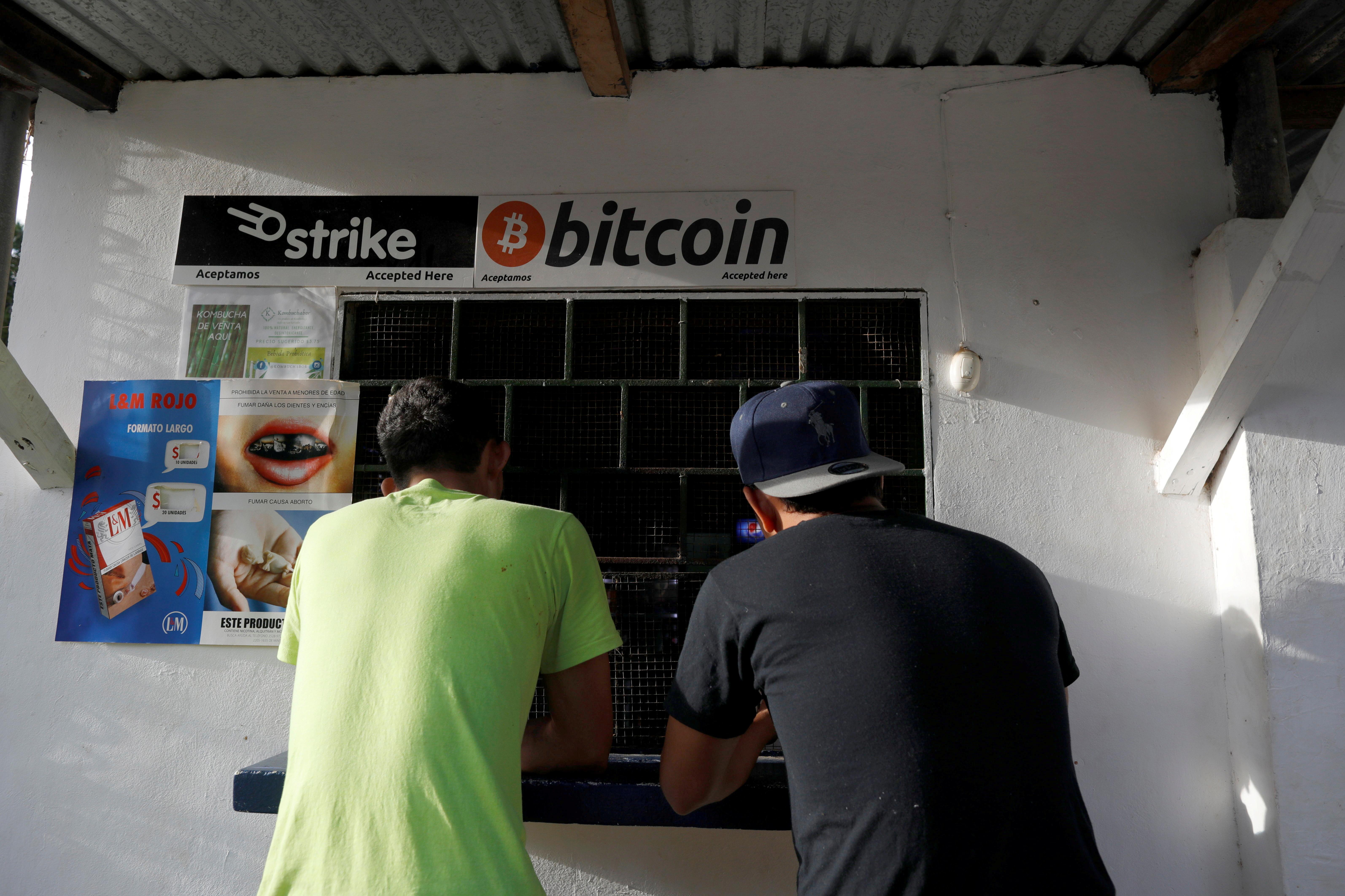 Men buy snacks at a store where bitcoins are accepted at El Zonte Beach in Chiltiupan, El Salvador June 16, 2021. REUTERS/Jose Cabezas/File Photo