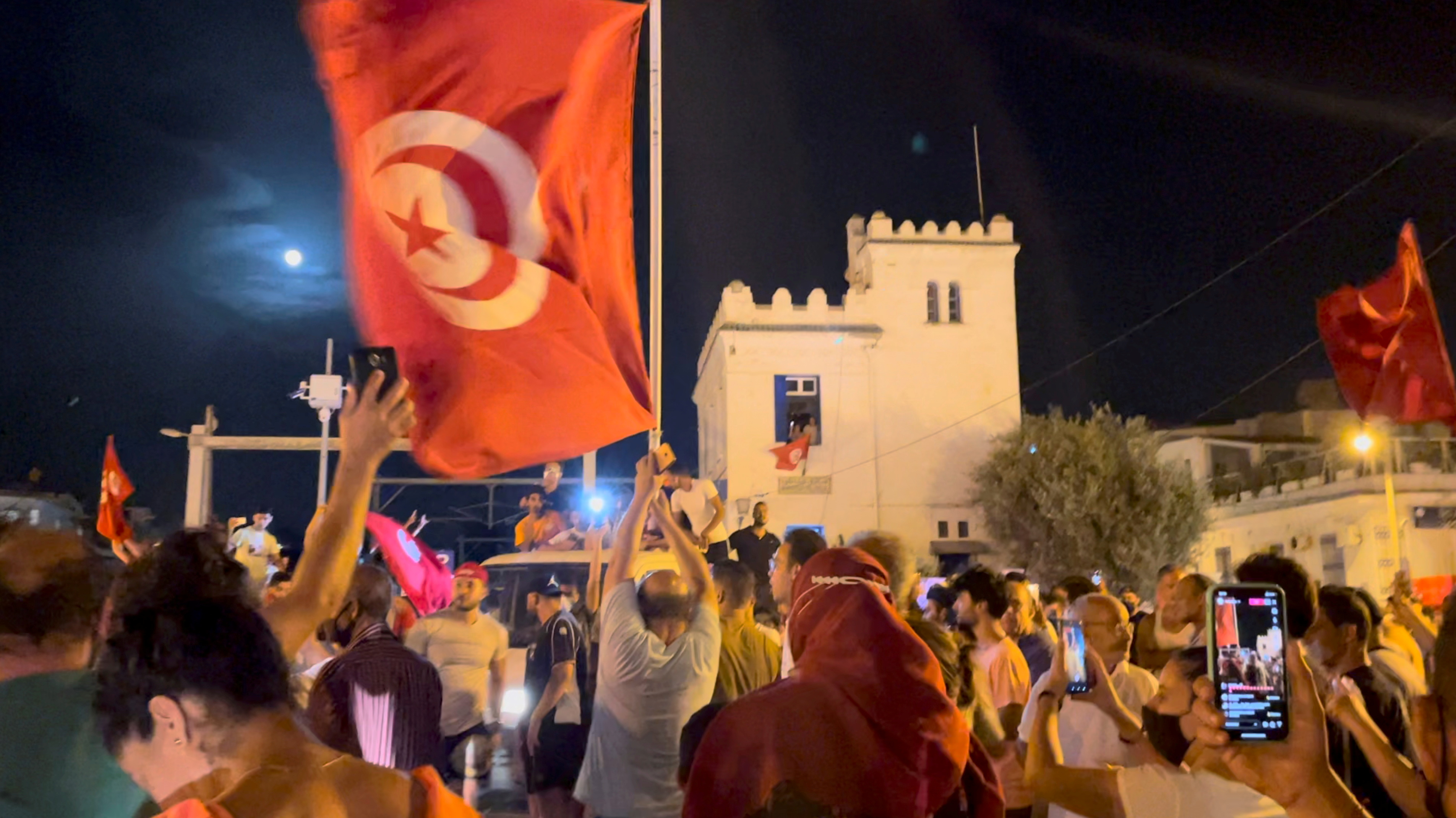 Crowds gather on the street after Tunisia's president suspended parliament, in La Marsa, near Tunis, Tunisia July 26, 2021, in this still image obtained from a social media video. Layli Foroudi/via REUTERS