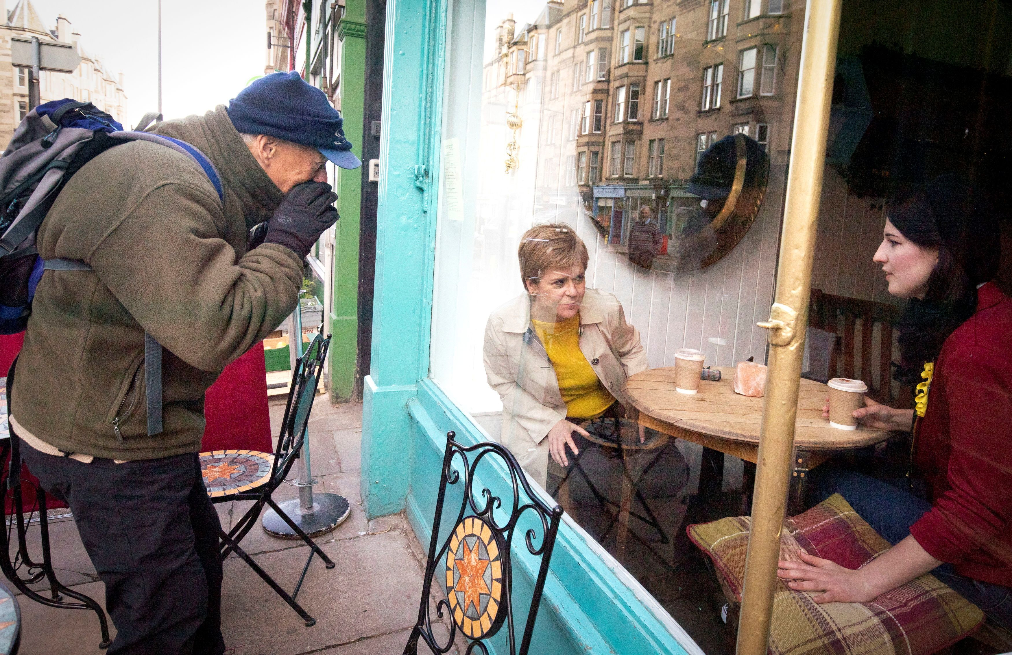 A member of the public tries to speak with Scotland's First Minister and leader of the Scottish National Party (SNP), Nicola Sturgeon, through a coffee shop window as she campaigns for the Scottish parliamentary election in Edinburgh, Britain, April 30, 2021. Jane Barlow/Pool via REUTERS