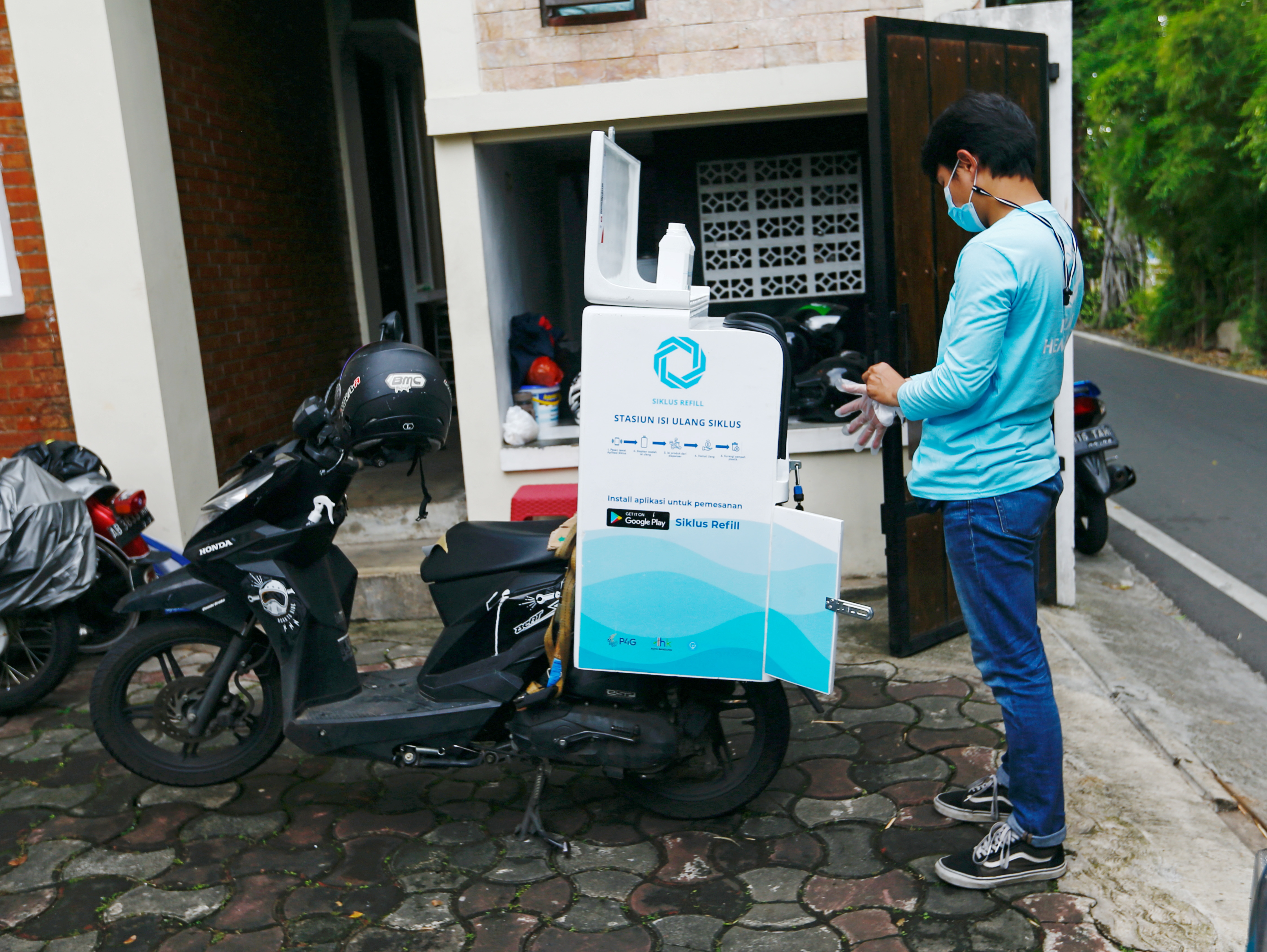 A deliveryman from Siklus, a start-up company which refills household products in a bid to reduce plastic waste, arrives at a customer's house in Jakarta, Indonesia, May 19, 2021. Picture taken May 19, 2021 REUTERS/Ajeng Dinar Ulfiana