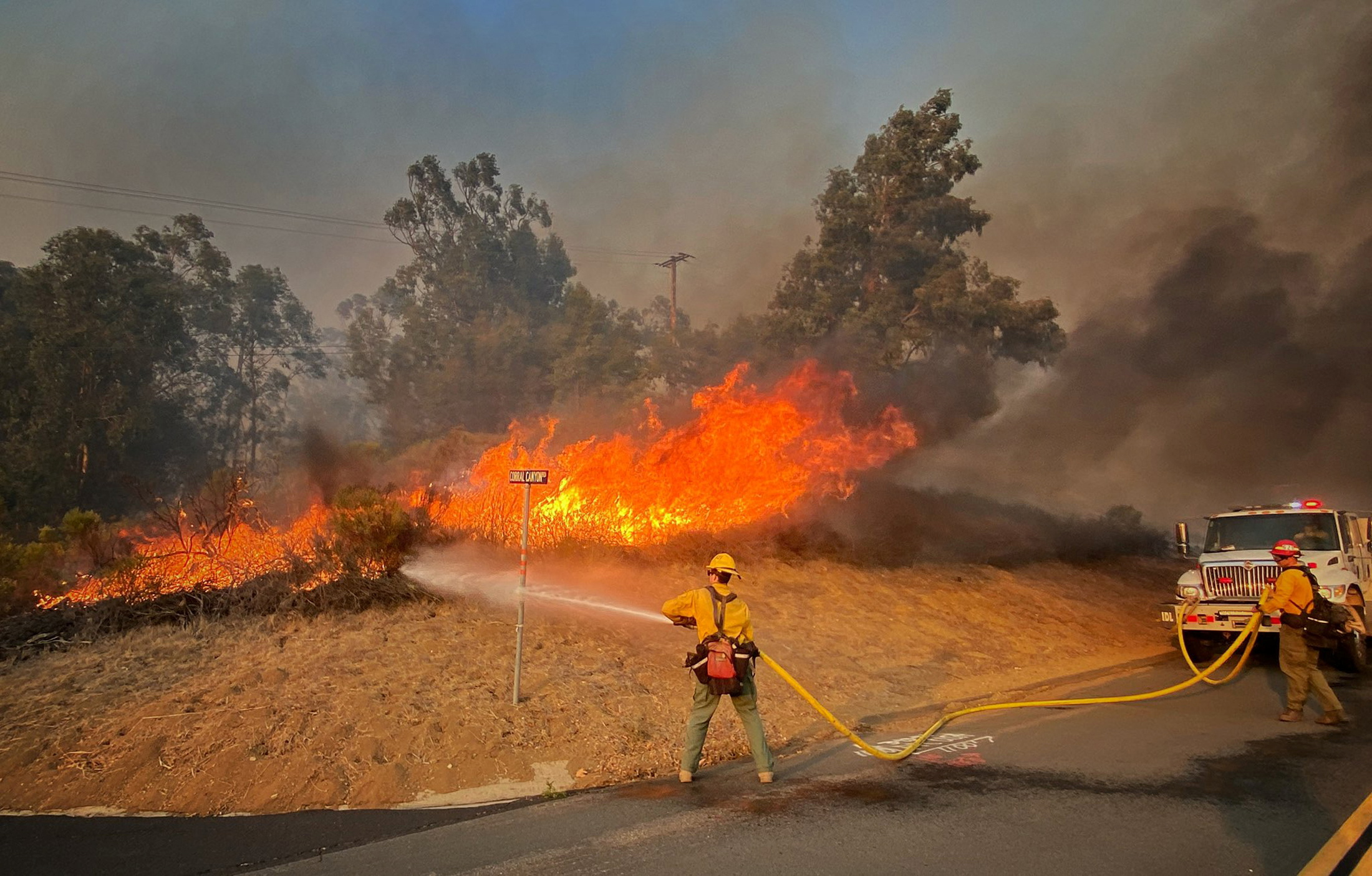Firefighters work on a roadside fire off Calle Real near Refugio Road, while battling the Alisal Fire west of Capitan, California, U.S. October 12, 2021. Mike Eliason/SBCo FD/Handout via REUTERS.