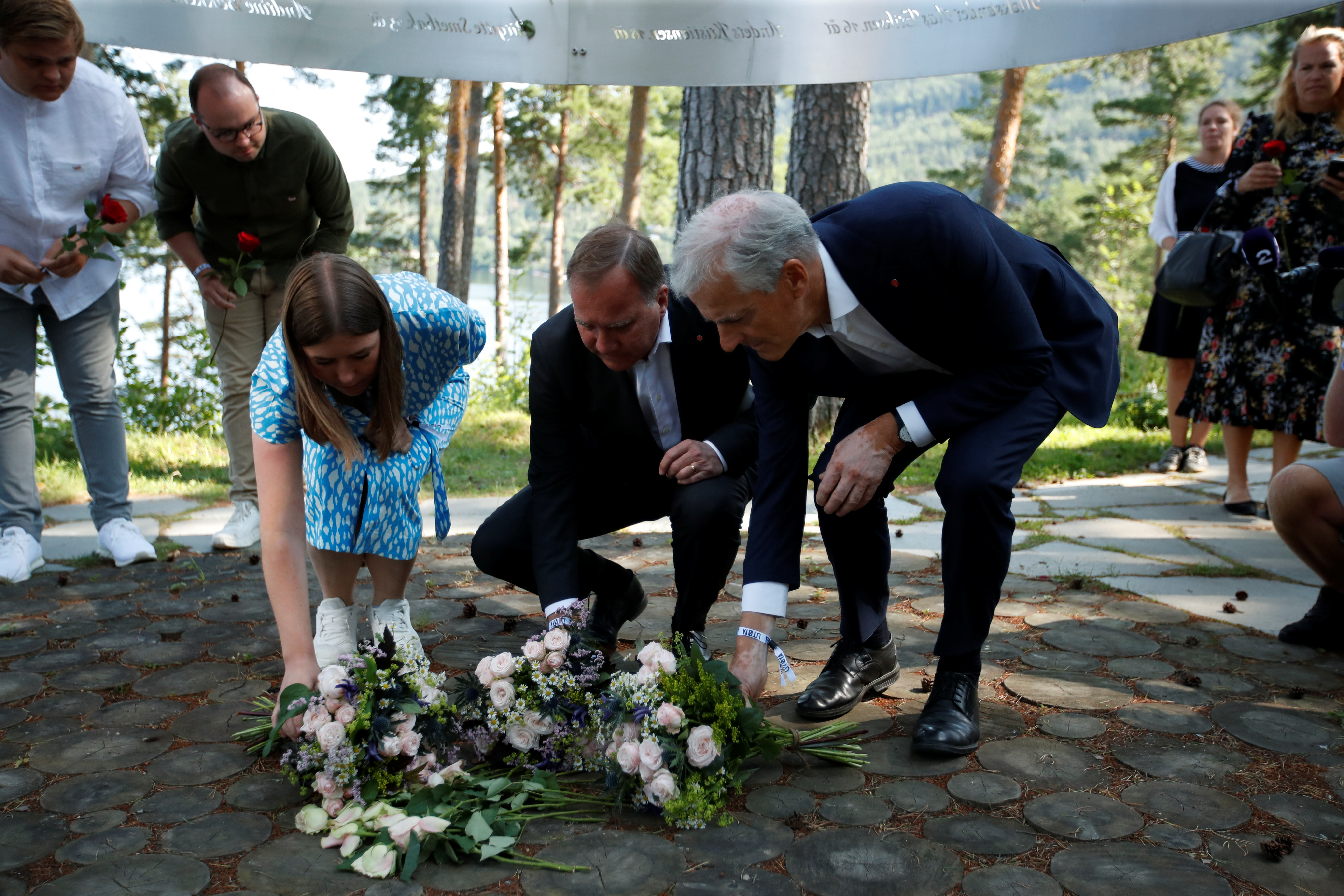 Leader of AUF Party in Norway and a survivor of the 2011 shooting, Astrid Hoem, Prime Minister of Sweden Stefan Lofven and a leader of the Norwegian Labor Party Jonas Gahr Store lay flowers at the memorial on Utoeya island the day before the 10th anniversary of the terrorist attack, in Utoeya, Norway July 21, 2021 Beate Oma Dahle/NTB/via REUTERS