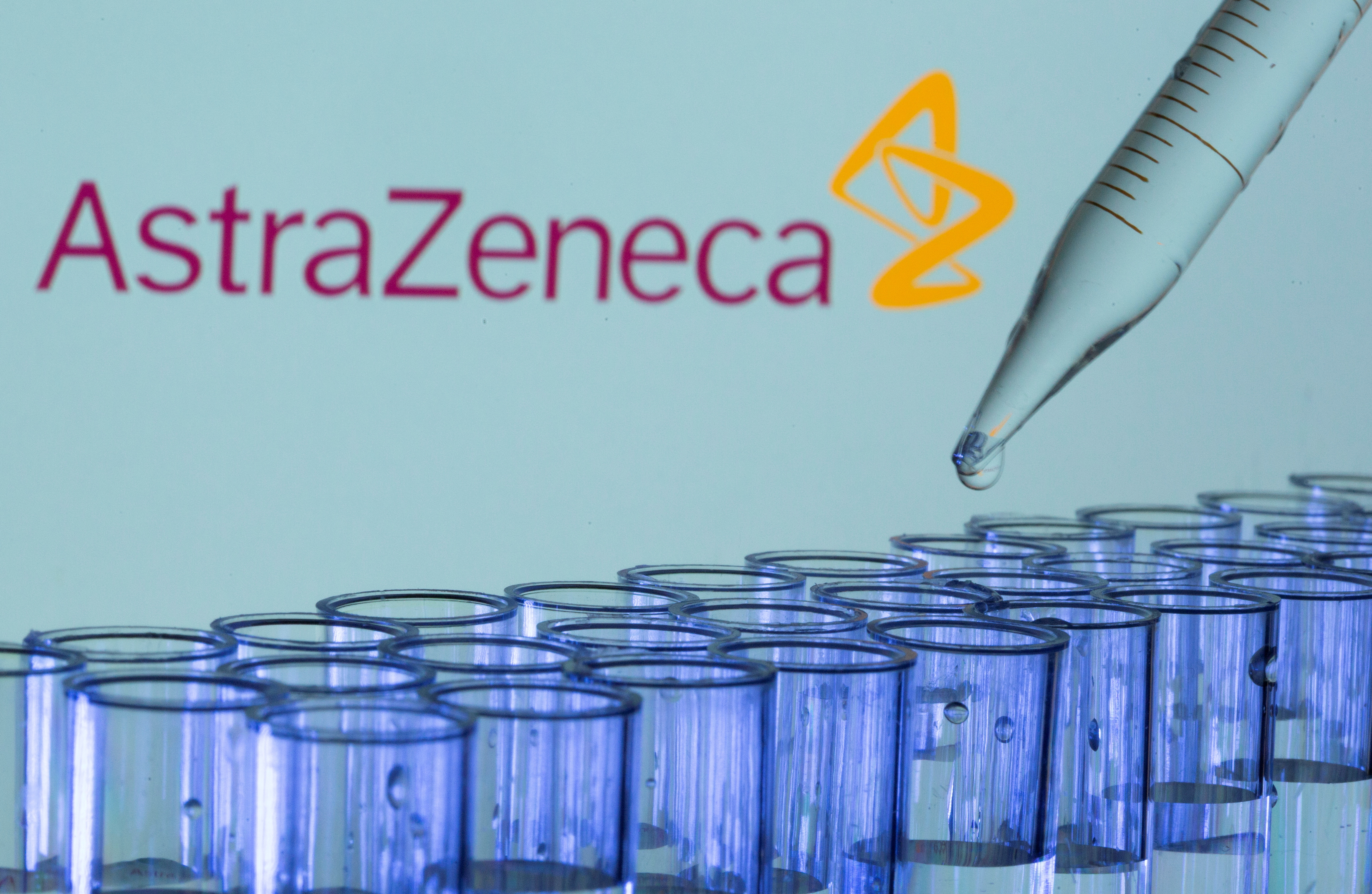 Test tubes are seen in front of a displayed AstraZeneca logo in this illustration taken, May 21, 2021. REUTERS/Dado Ruvic/Illustration/File Photo