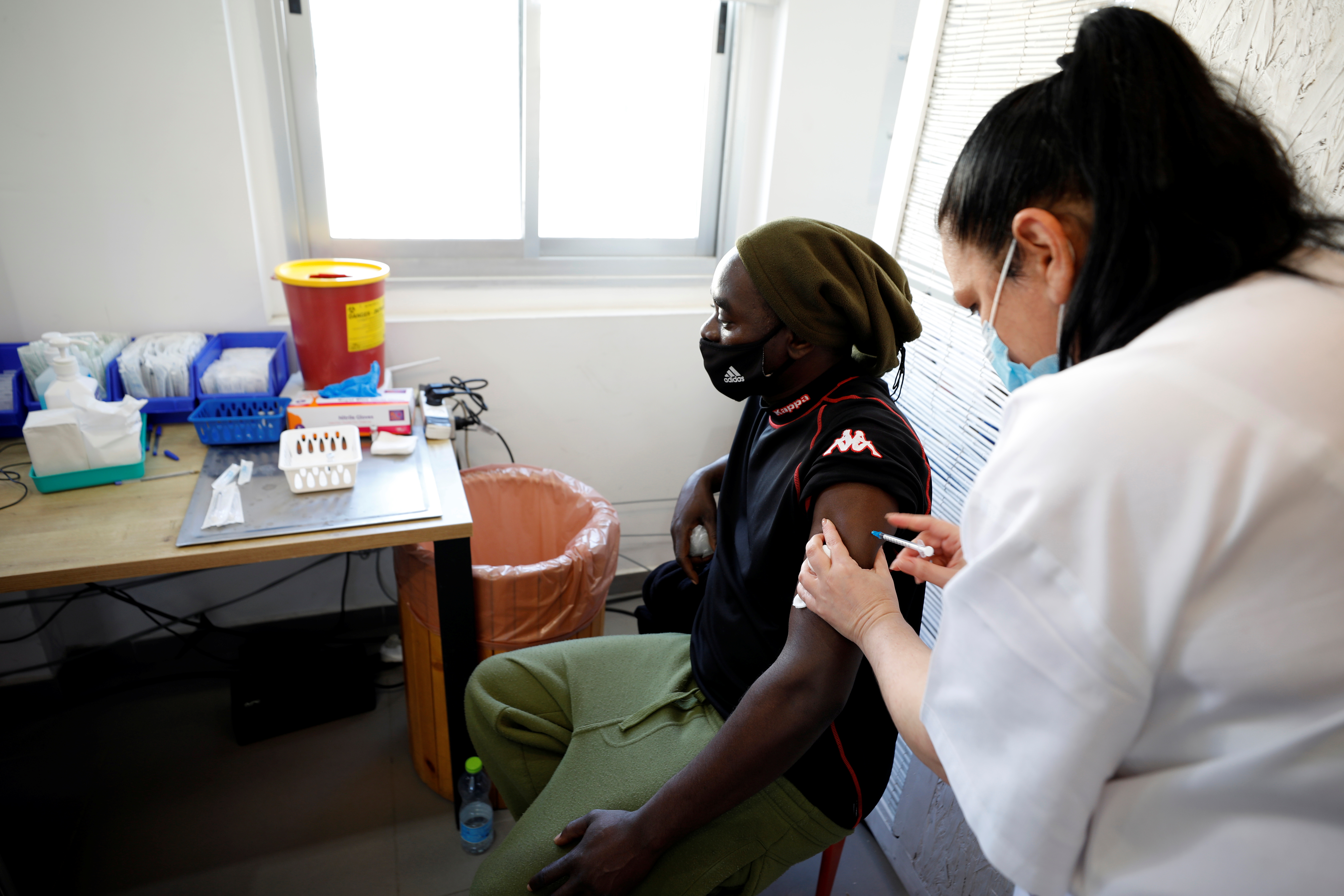 A medical worker administers a vaccination against the coronavirus disease (COVID-19) at a newly-opened centre in a neighbourhood with a high residency of foreign nationals, including migrant workers, in Tel Aviv, Israel February 9, 2021. REUTERS/Amir Cohen