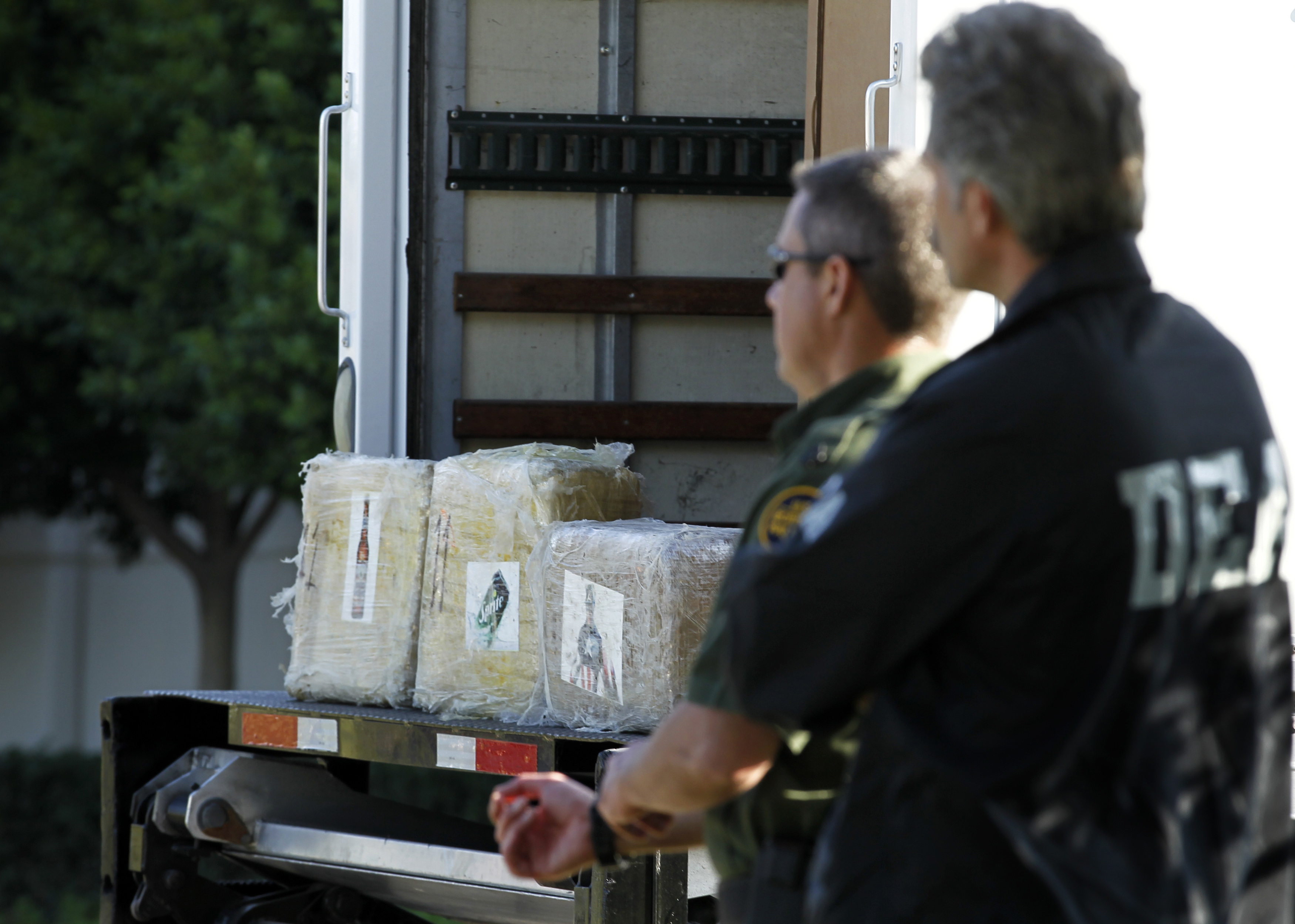 A Drug Enforcement Administration (DEA) agent and a border patrol officer stand next to marijuana seized in Otay Mesa, California. REUTERS/Mike Blake