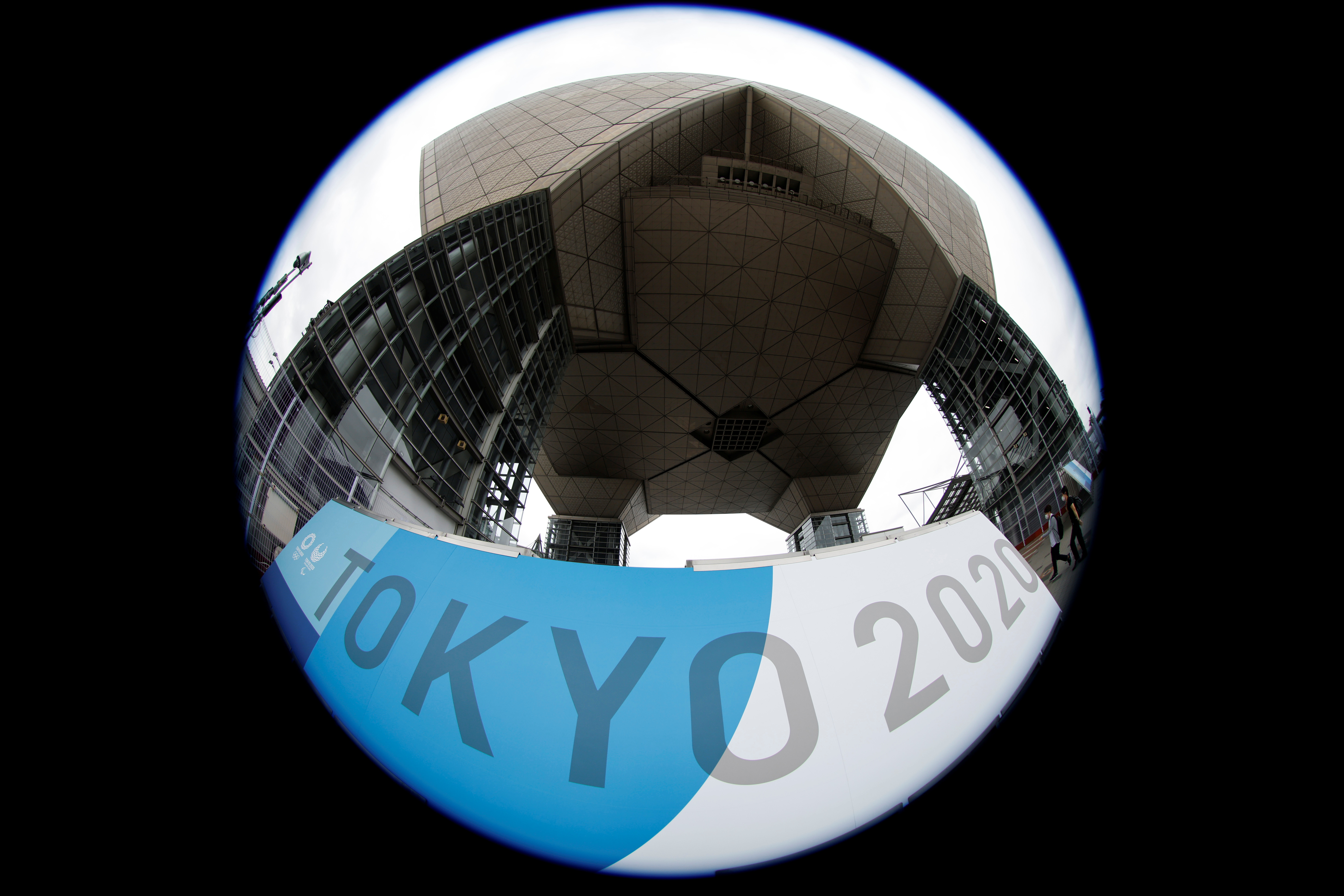 People walk past a sign for the 2020 Tokyo Olympic Games that have been postponed to 2021 due to the coronavirus disease (COVID-19) pandemic, at the IBC/MPC media center at Tokyo Big Sight exhibition center in Tokyo, Japan June 30, 2021.  REUTERS/Fabrizio Bensch