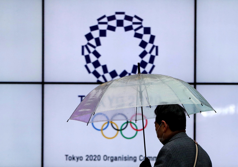 Một người đàn ông đeo khẩu trang bảo vệ đi ngang qua màn hình hiển thị biểu trưng của Thế vận hội Olympic Tokyo 2020 đã bị hoãn lại đến năm 2021 do dịch bệnh coronavirus (COVID-19) bùng phát ở Tokyo, Nhật Bản ngày 23 tháng 1 năm 2021. REUTERS / Issei Kato
