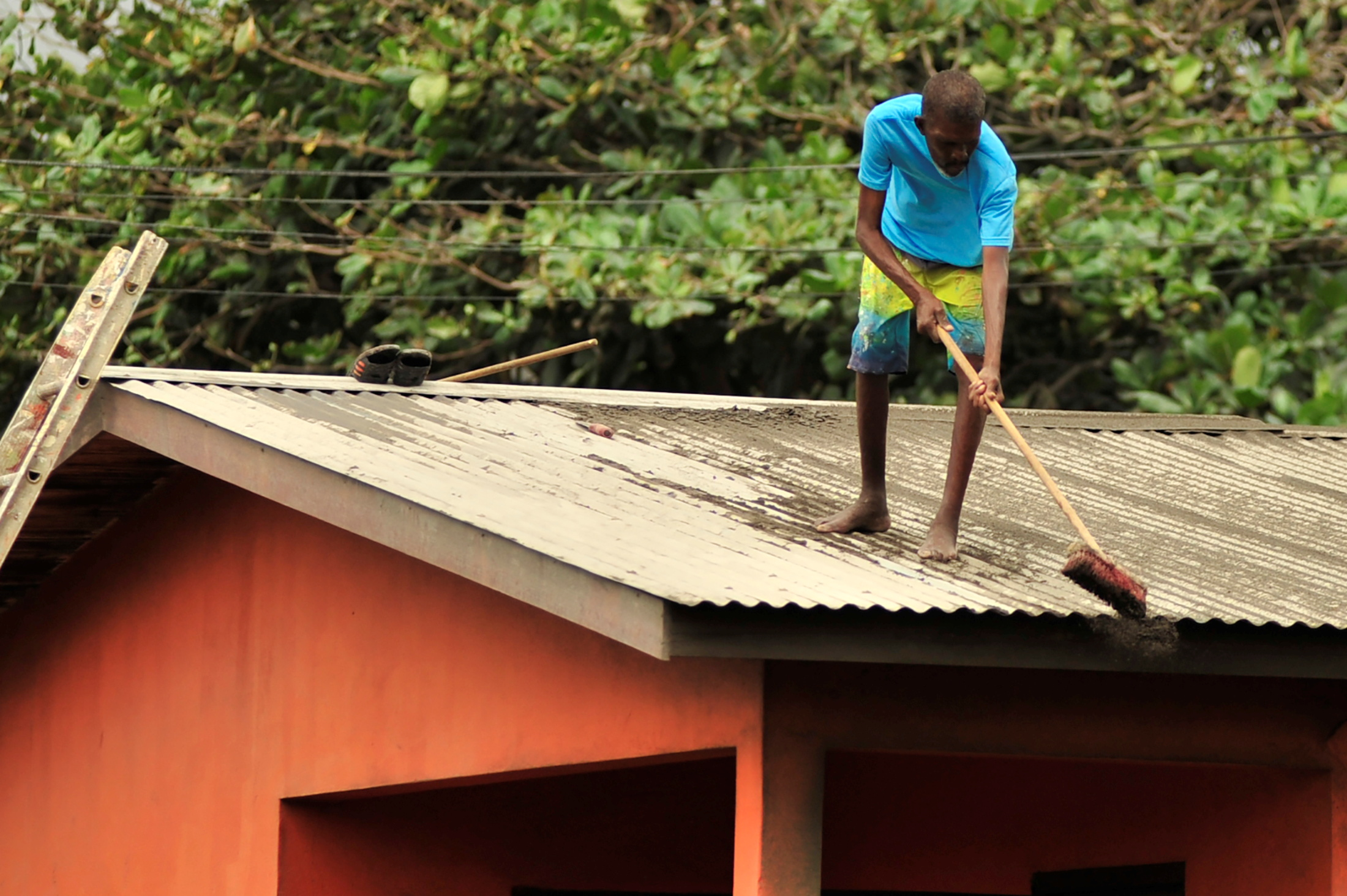 A local residents clears ash from a roof after a series of eruptions from La Soufriere volcano covered the area with a thick layer of ash in Georgetown, Saint Vincent and the Grenadines, April 13, 2021.  REUTERS/Robertson S. Henry