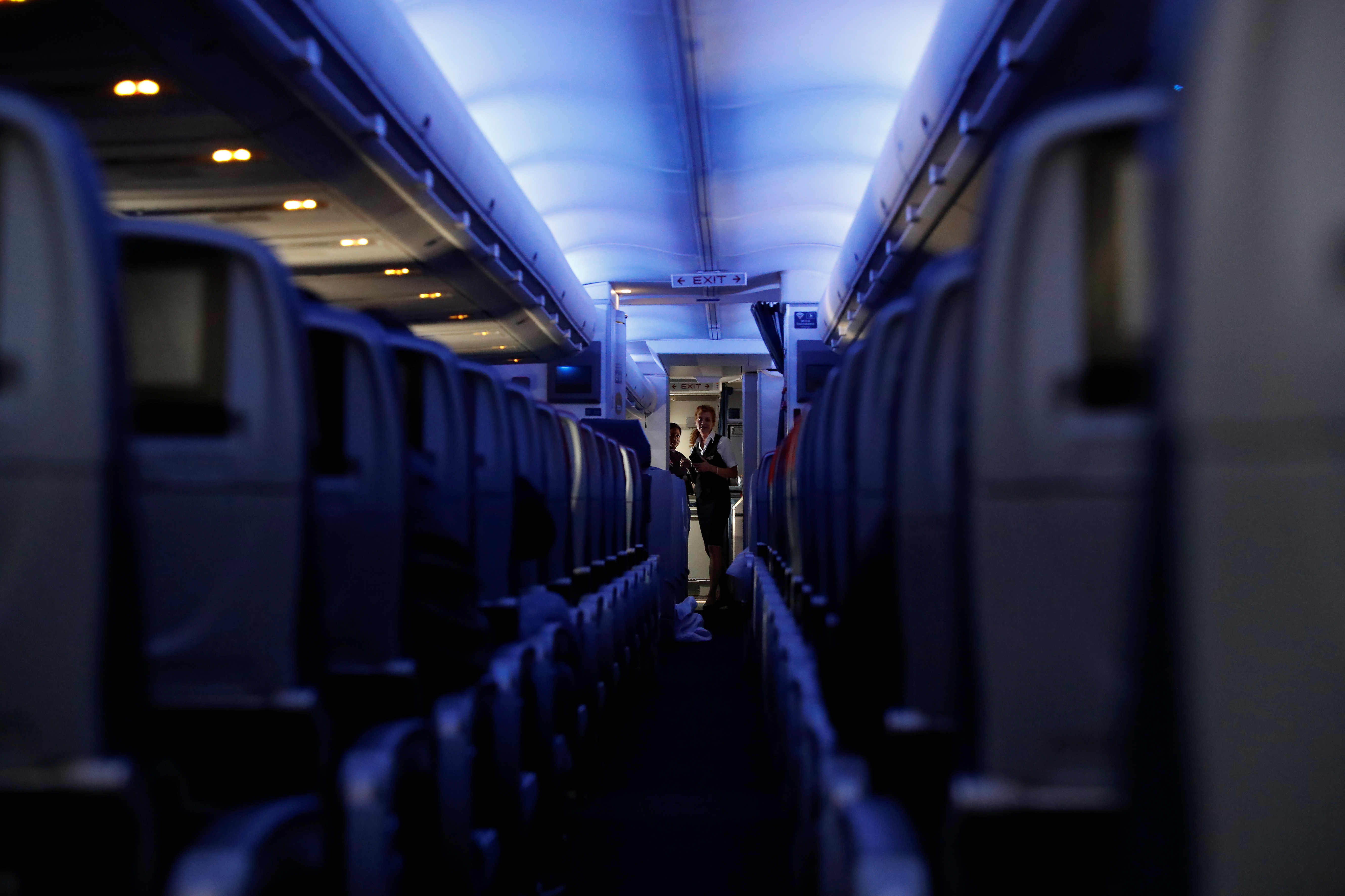 Flight attendants stand at the end of rows of empty seats aboard a Delta flight, as coronavirus disease (COVID-19) disruption continues across the global industry, from New York's JFK International Airport to San Francisco, California, U.S., March 17, 2020. REUTERS/Shannon Stapleton