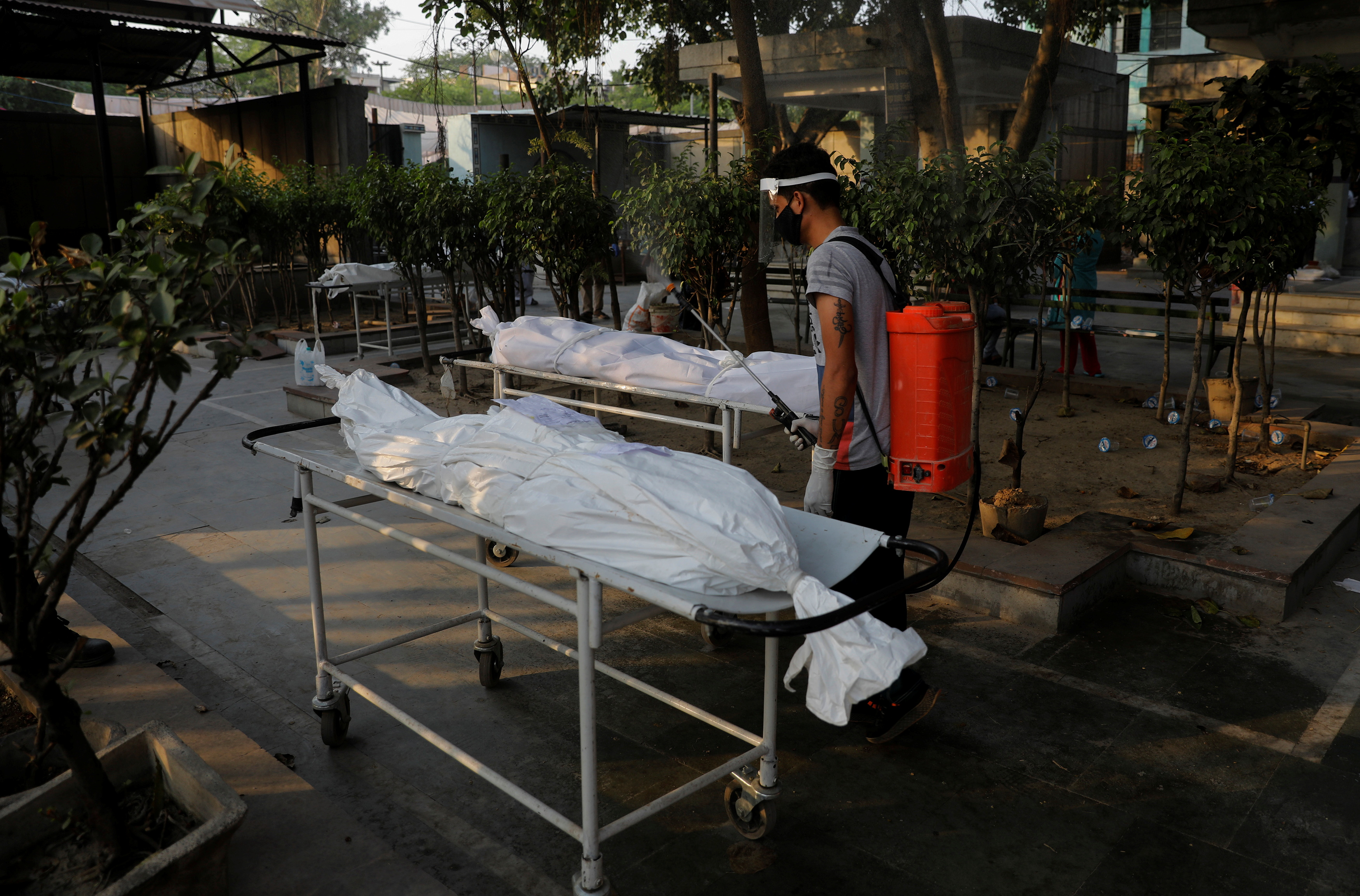 A municipal worker sprays disinfectant on the bodies of victims who died due to the coronavirus disease (COVID-19), at a crematorium in New Delhi, India, May 10, 2021. REUTERS/Adnan Abidi