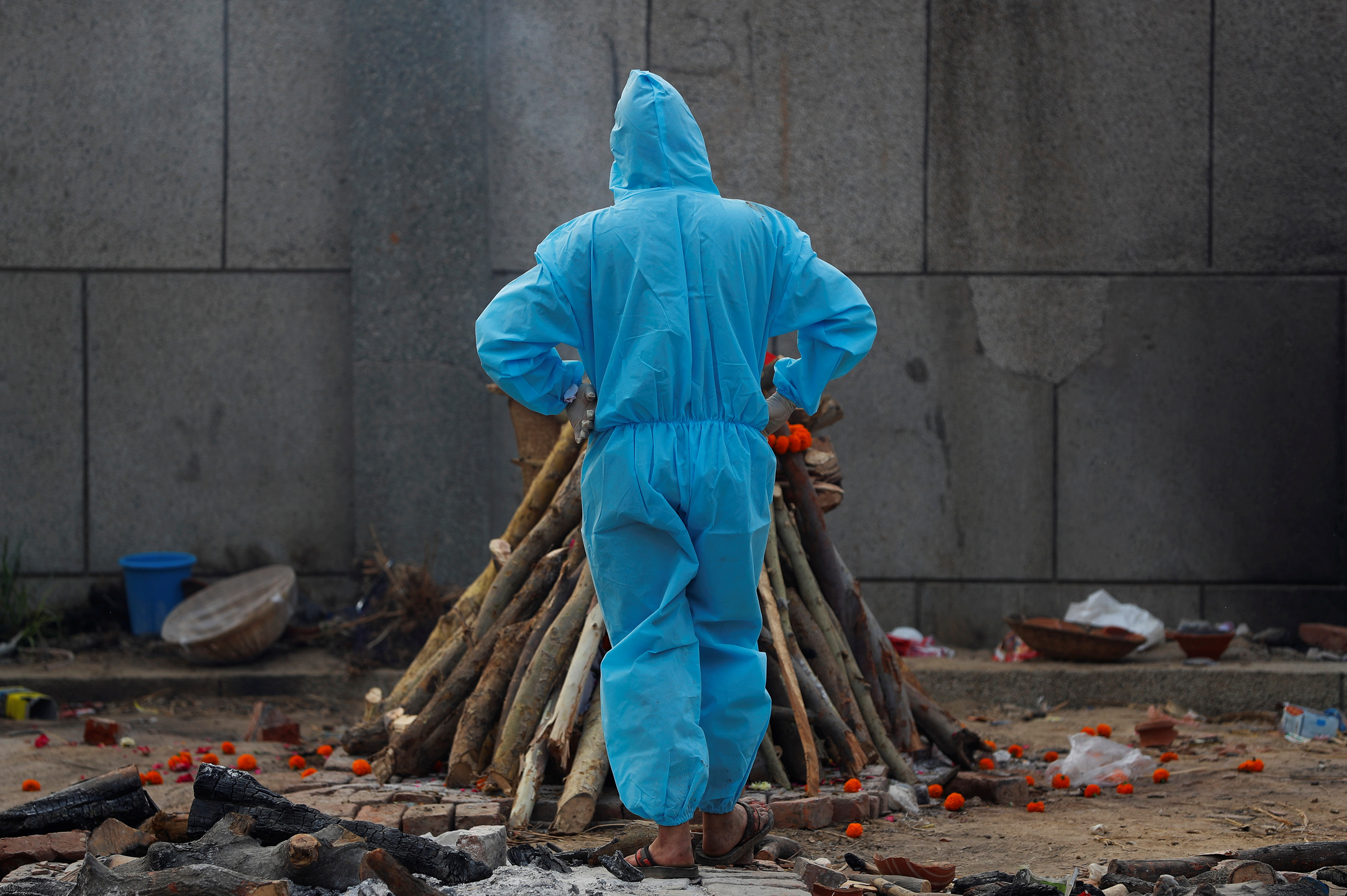 A man wearing personal protective equipment (PPE) stands next to a burning funeral pyre of a relative, who died from the coronavirus disease (COVID-19), before his cremation, at a crematorium in New Delhi, India May 5, 2021. REUTERS/Adnan Abidi