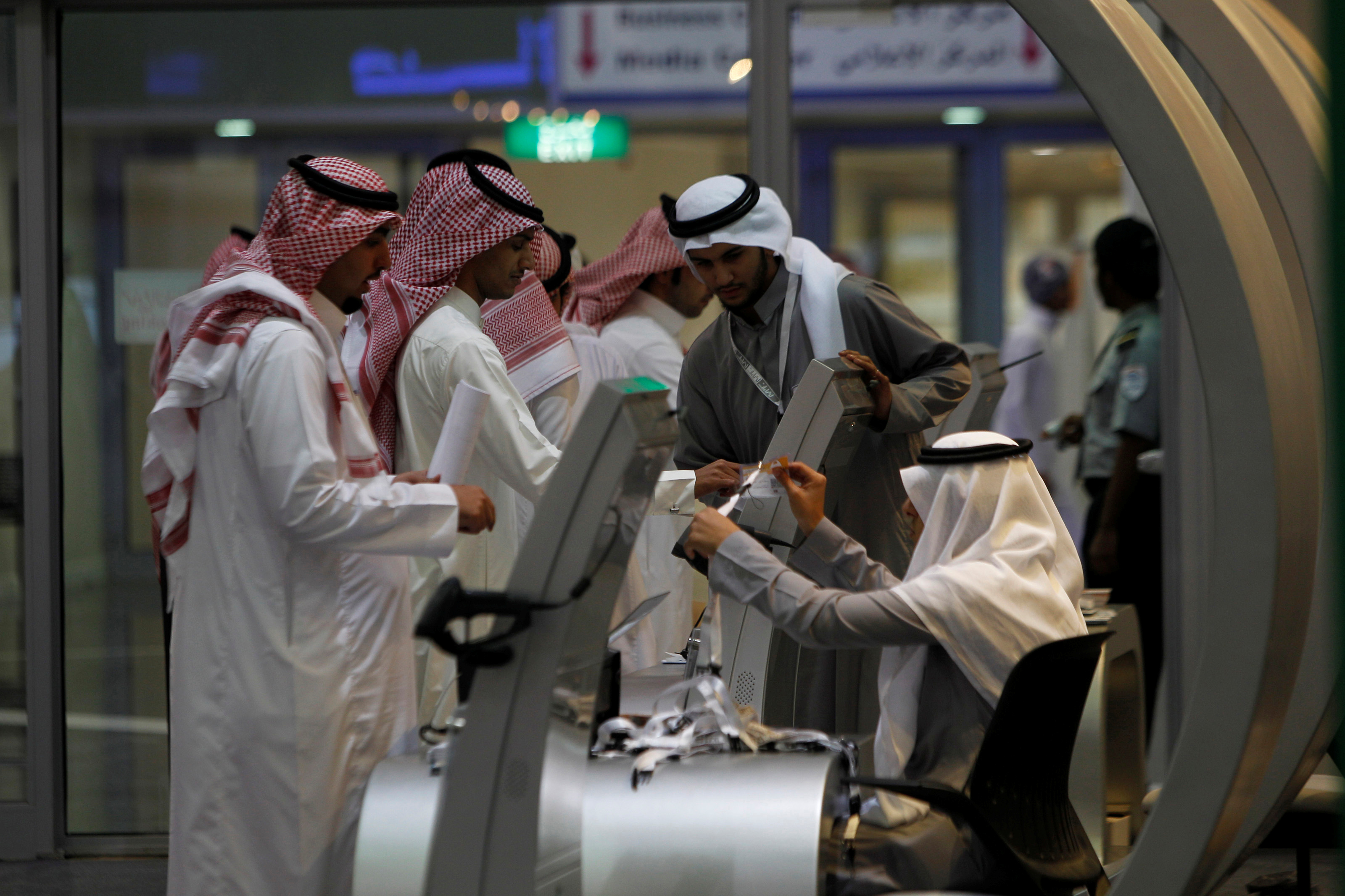 Jobseekers stand in line to talk with a recruiter at a booth at a job fair in Riyadh, January 29, 2012. REUTERS/Fahad Shadeed/File Photo