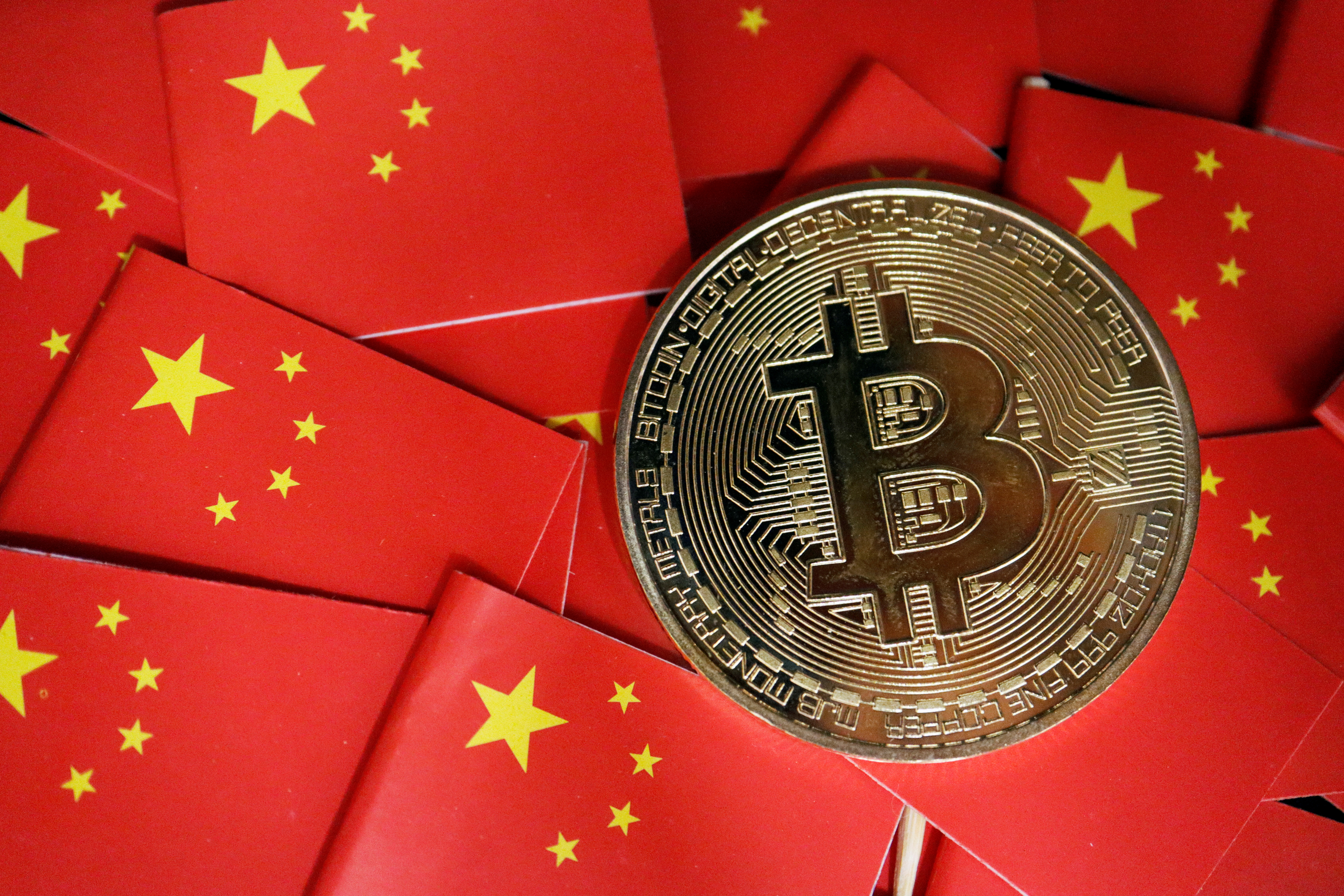 A representation of Bitcoin cryptocurrency is seen amid China's flags in this illustration picture taken September 27, 2021. REUTERS/Florence Lo/Illustration