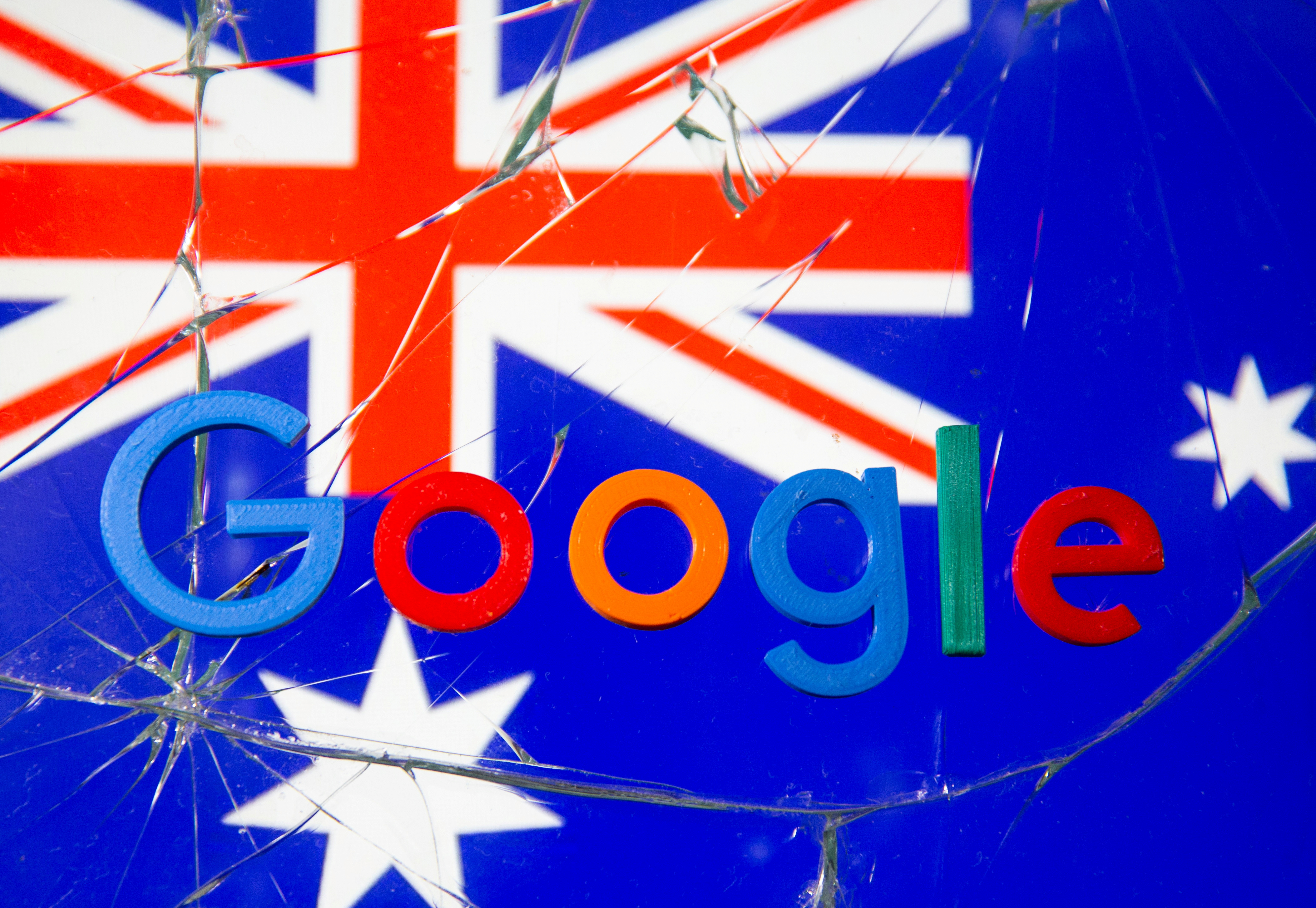 A 3D printed Google logo is placed on broken glass in front of displayed Australian flag  in this illustration taken, January 22, 2021. REUTERS/Dado Ruvic/Illustration/File Photo