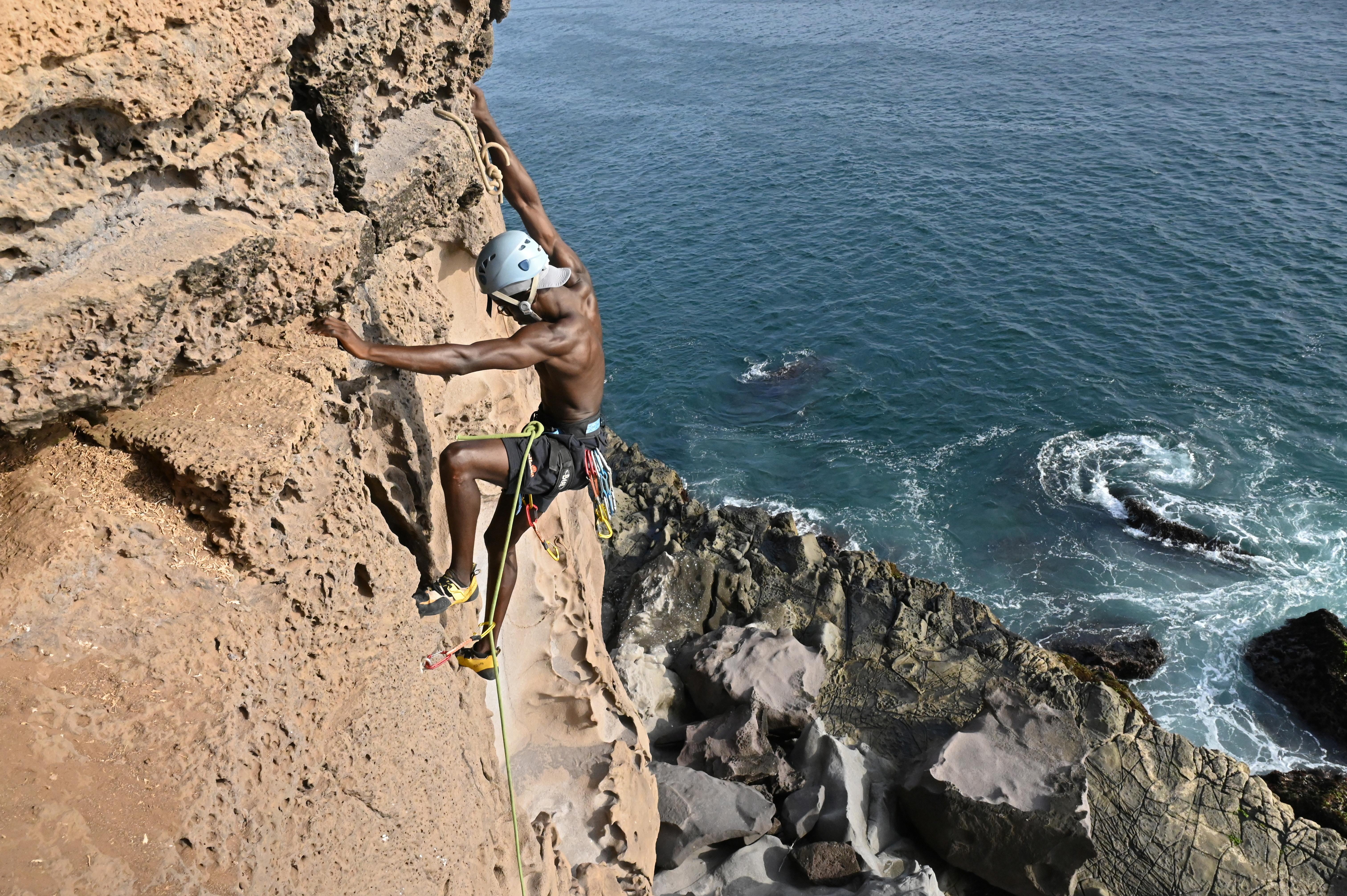 Senegalese rock climber Abasse Wane climbs a rock wall at the Mamelles cliffs in Dakar, Senegal, June 27, 2021.  REUTERS/Cooper Inveen