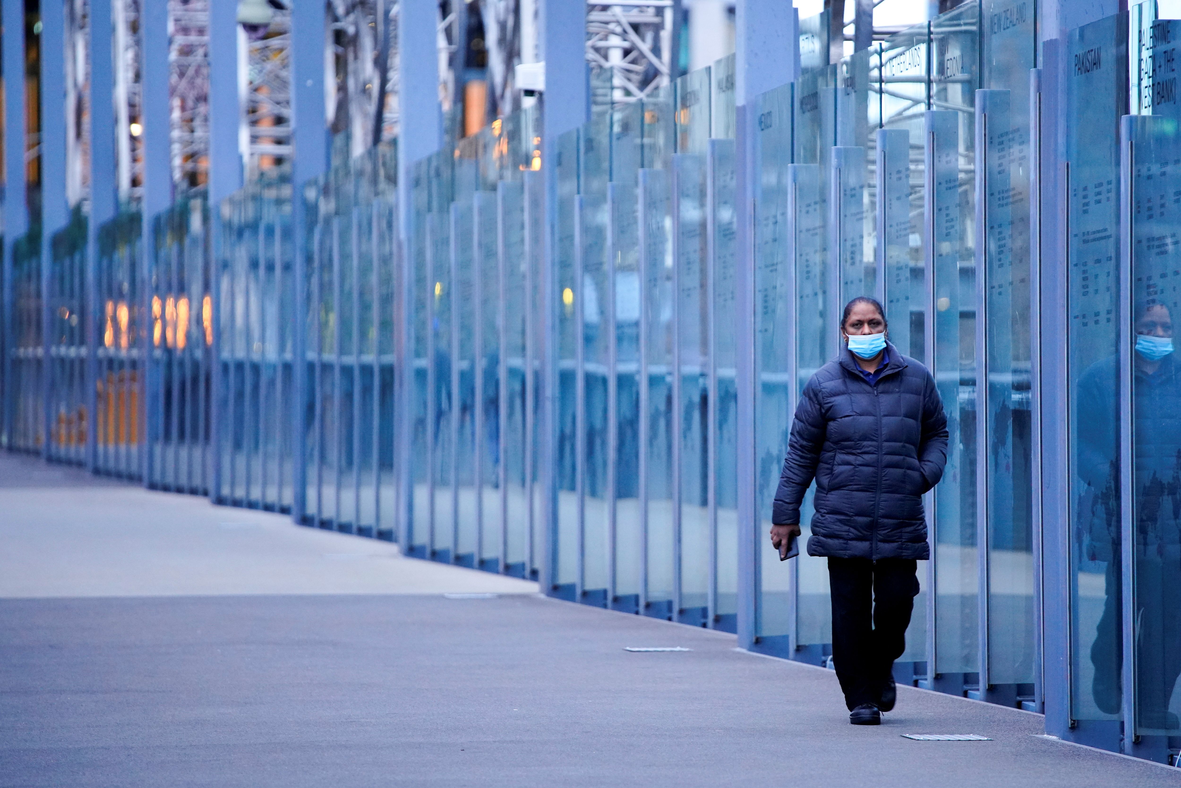 A woman wearing a protective face mask walks along a deserted city bridge during morning commute hours on the first day of a lockdown as the state of Victoria looks to curb the spread of a coronavirus disease (COVID-19) outbreak in Melbourne, Australia, July 16, 2021.  REUTERS/Sandra Sanders