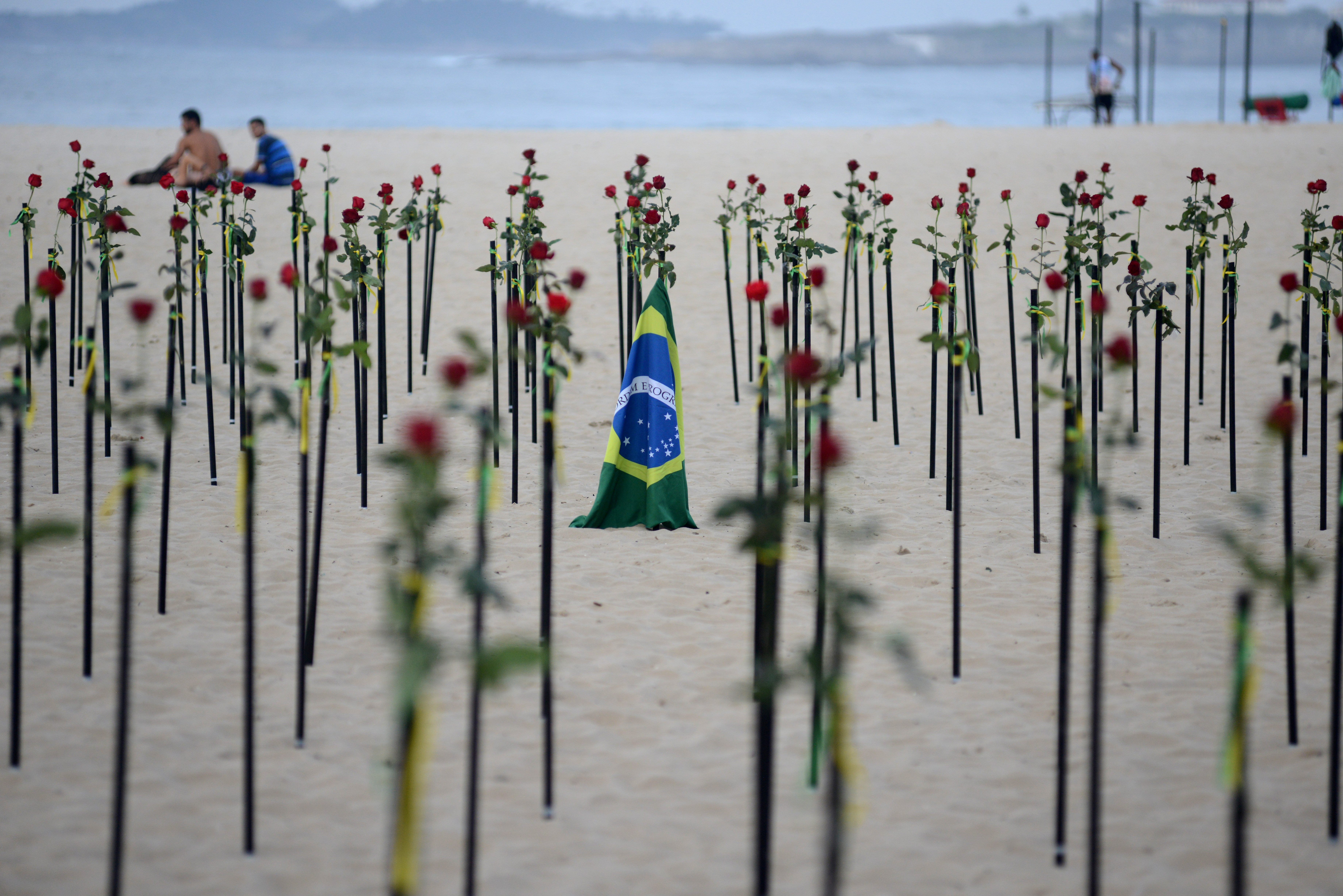 A Brazilian national flag is seen amidst red flowers placed by Rio de Paz NGO on Copacabana beach to pay tribute to the Brazil's half a million COVID-19 deaths in Rio de Janeiro, Brazil, June 20, 2021. REUTERS/Lucas Landau