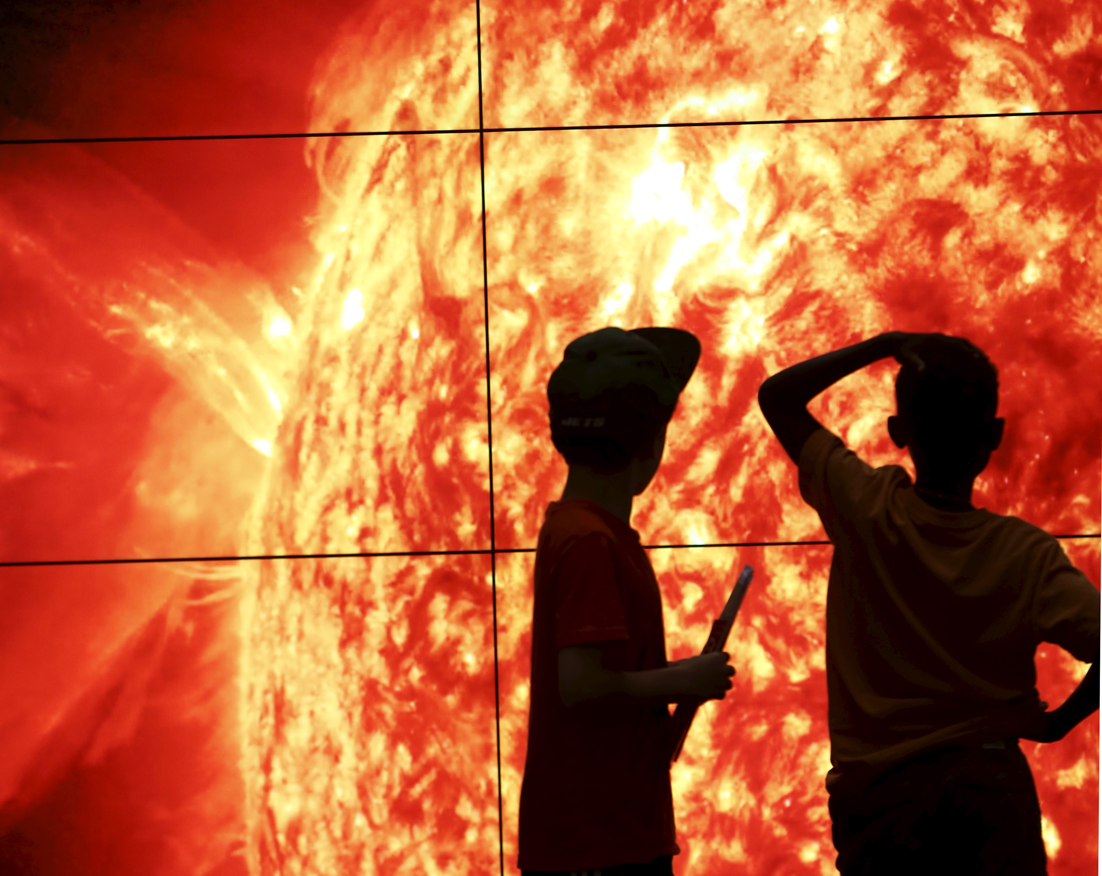 Two boys at the Smithsonian National Air and Space Museum look at images that are 48 hours old, coming back from the sun, in Washington, September 1, 2015. The sun's images, from NASA's Solar Dynamic Observatory, show four different wavelengths and deliver data on the sun's influence on earth. REUTERS/Gary Cameron
