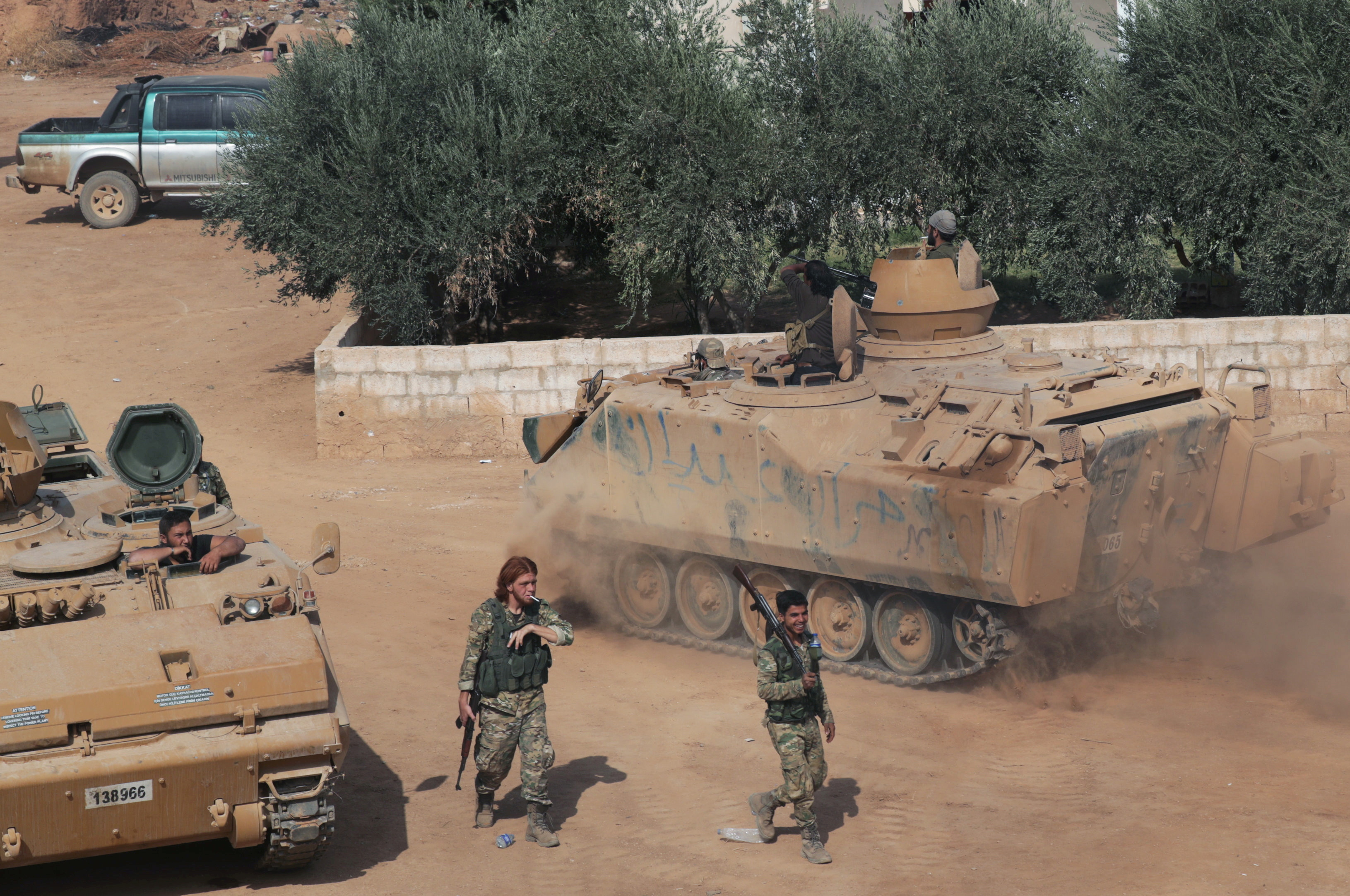 Turkey-backed Syrian rebel fighters walk past military tanks as they gather near the border town of Tal Abyad, Syria October 24, 2019. REUTERS/Khalil Ashawi/File Photo