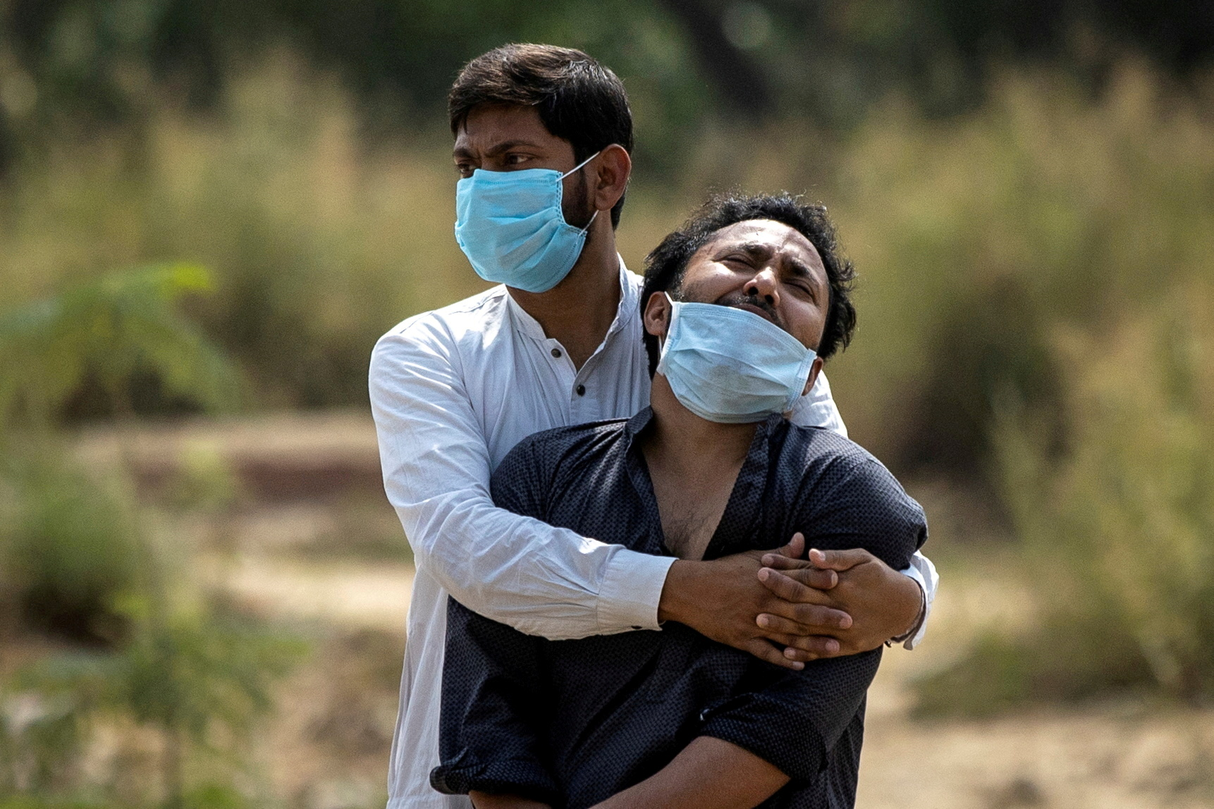 A man is consoled by his relative as he sees the body of his father, who died from complications related to the coronavirus disease (COVID-19), before his burial at a graveyard in New Delhi, India, April 16, 2021. REUTERS/Danish Siddiqui/File Photo