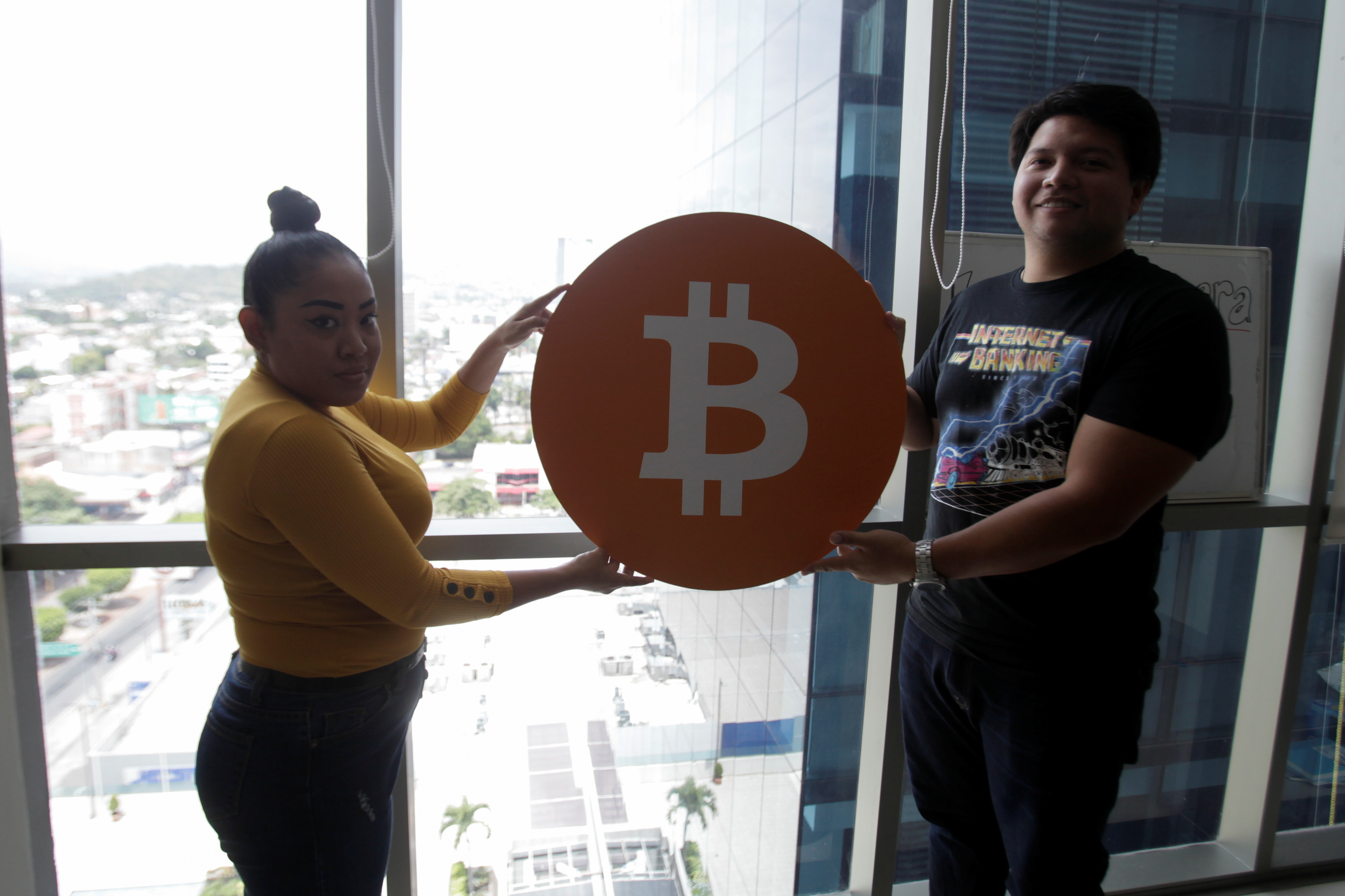 Juan Mayen, 28, chief executive of Honduran firm TGU Consulting Group, and Claudia Suazo pose for a photo holding a Bitcoin logo at the office of TGU where they installed the first cryptocurrency ATM machine in the country that allows users to acquire bitcoin and ethereum using the local lempira currency, in Tegucigalpa, Honduras August 27, 2021. REUTERS/Fredy Rodriguez