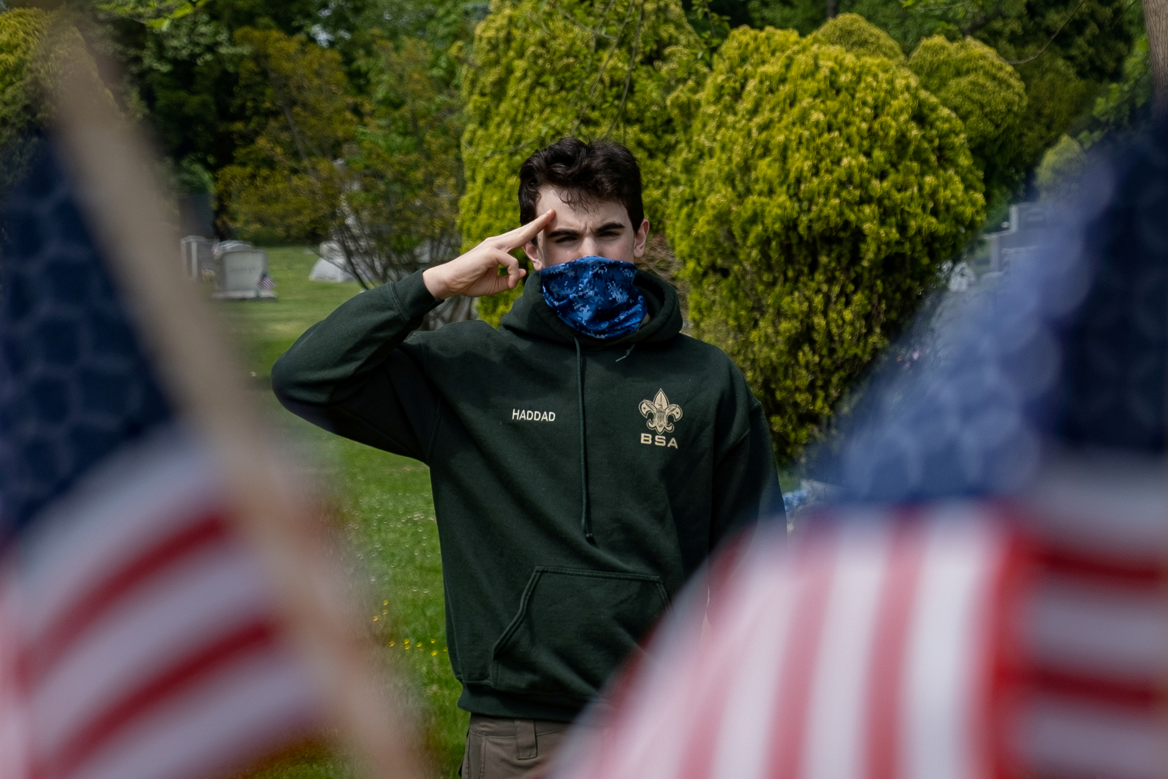 A member of Boy Scouts of America wearing a protective mask salutes at a ceremony for Veterans who are unable to give military honors during Memorial Day following the outbreak of the coronavirus disease (COVID-19) in the Staten Island borough of New York U.S., May 25, 2020. REUTERS/Jeenah Moon