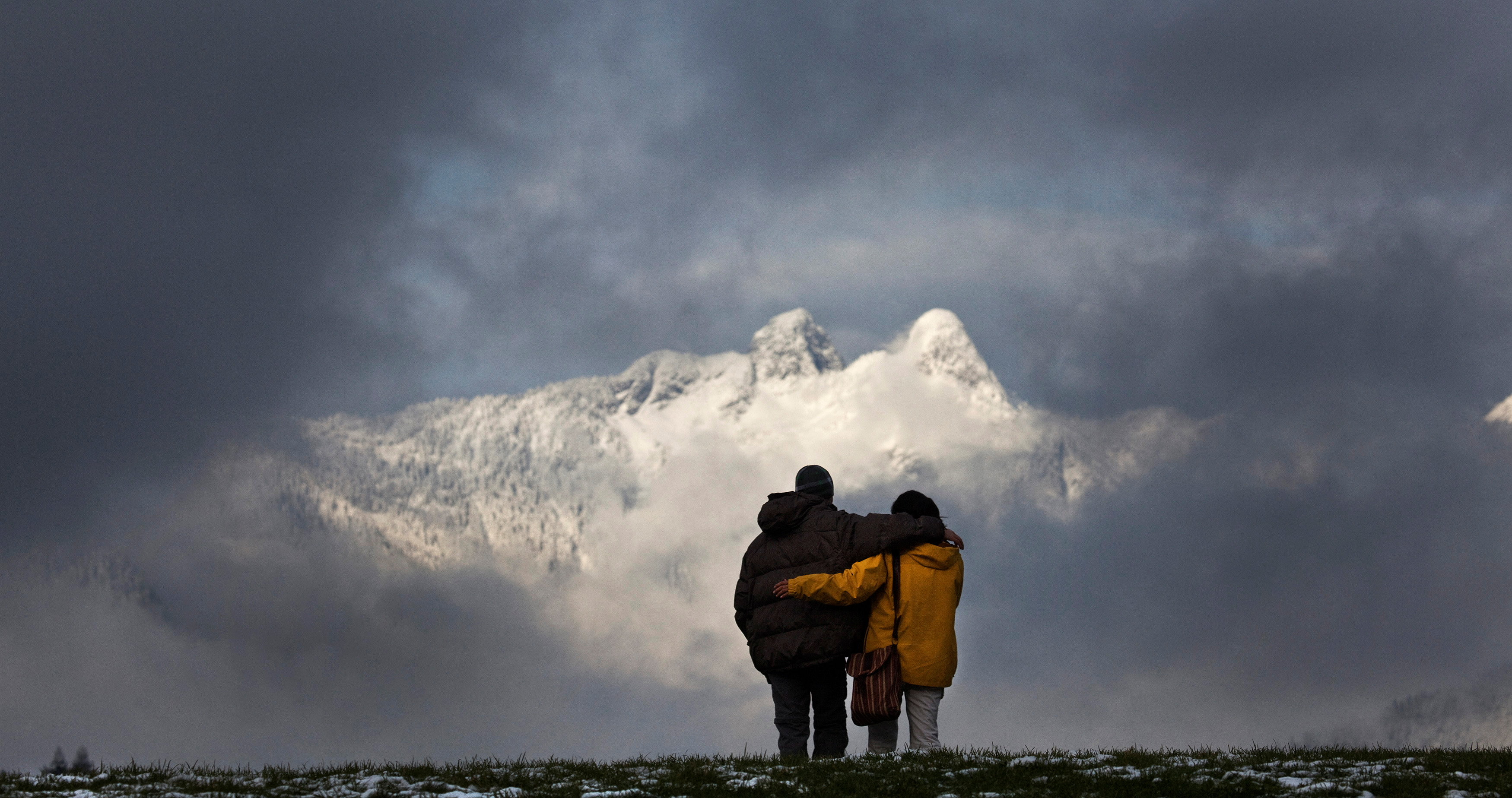 A couple walks arm-in-arm while visiting Capilano Park as the Lions Gate Mountain is seen through the clouds in North Vancouver, British Columbia November 20, 2010. REUTERS/Andy Clark
