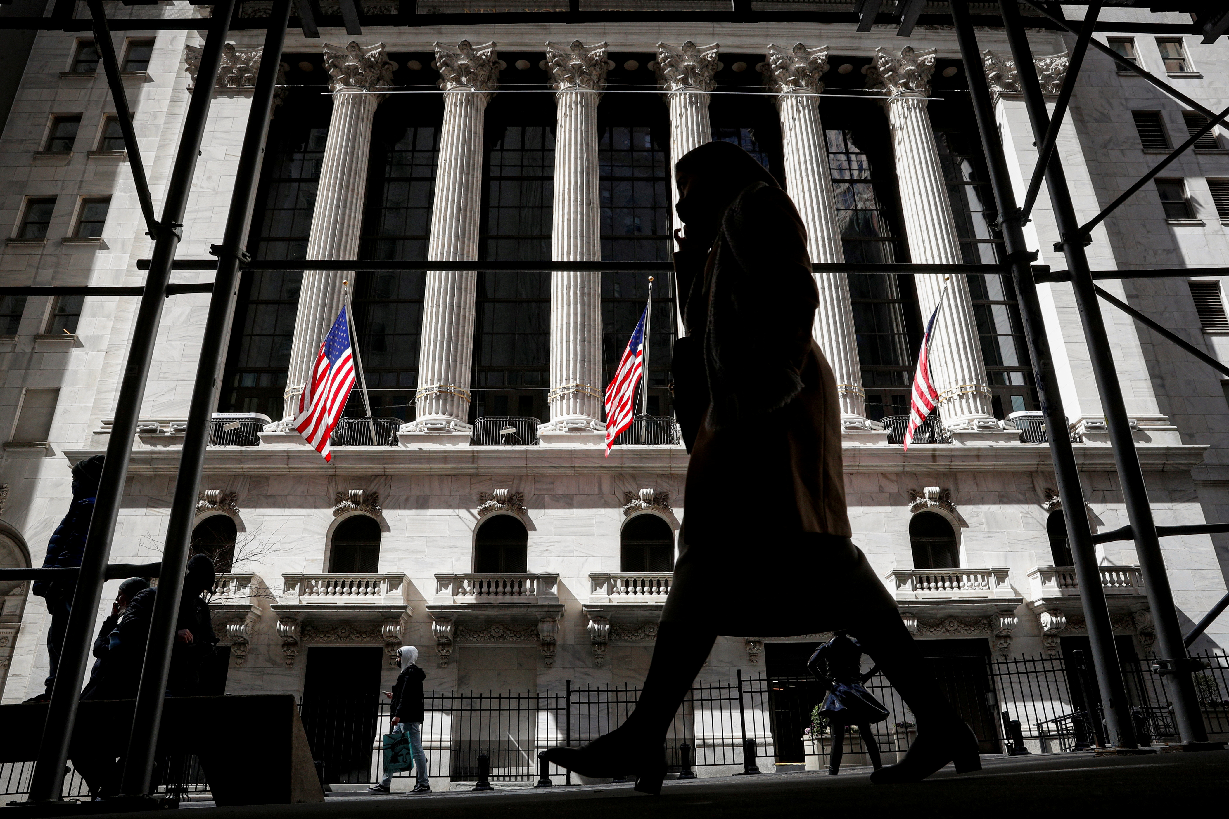 People are seen outside the New York Stock Exchange (NYSE) in New York City, U.S., March 19, 2021.  REUTERS/Brendan McDermid/File Photo