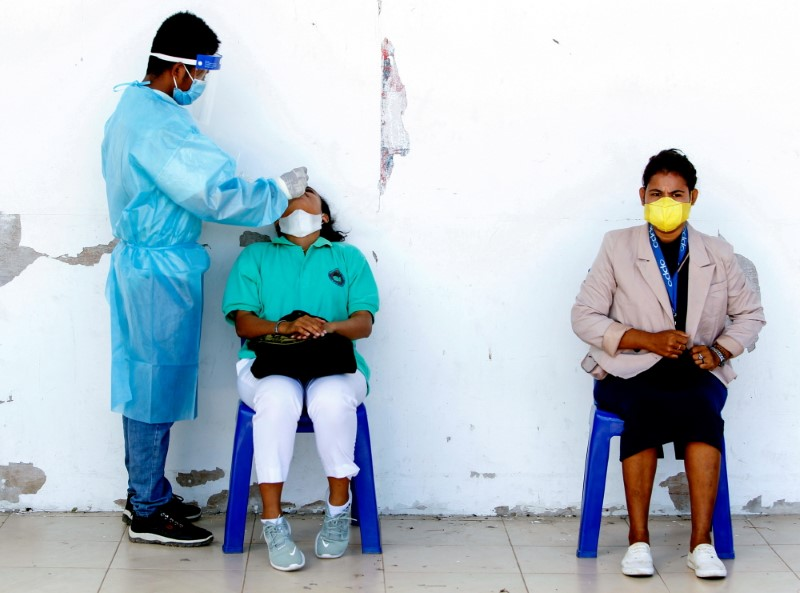 A medical worker wearing personal protective equipment (PPE) takes a swab sample from a person to be tested for coronavirus disease (COVID-19) in Dili, East Timor, August 10, 2021. REUTERS/Lirio da Fonseca