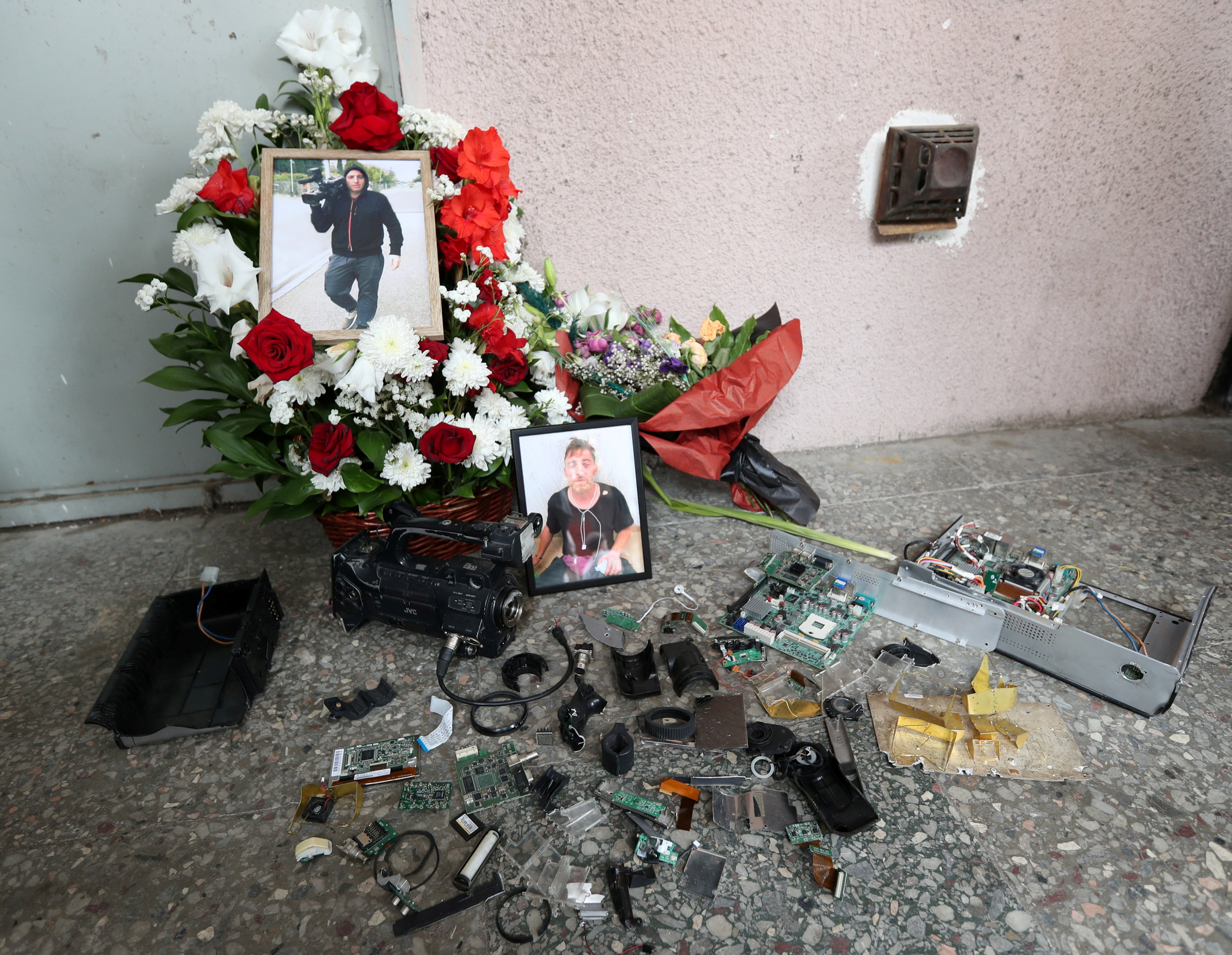 Portraits of journalist Alexander Lashkarava are placed next to a broken camera during his funeral in Tbilisi, Georgia July 13, 2021. Lashkarava was found dead at his home several days after he was beaten during attacks on LGBT+ activists in Tbilisi. REUTERS/Irakli Gedenidze/File Photo