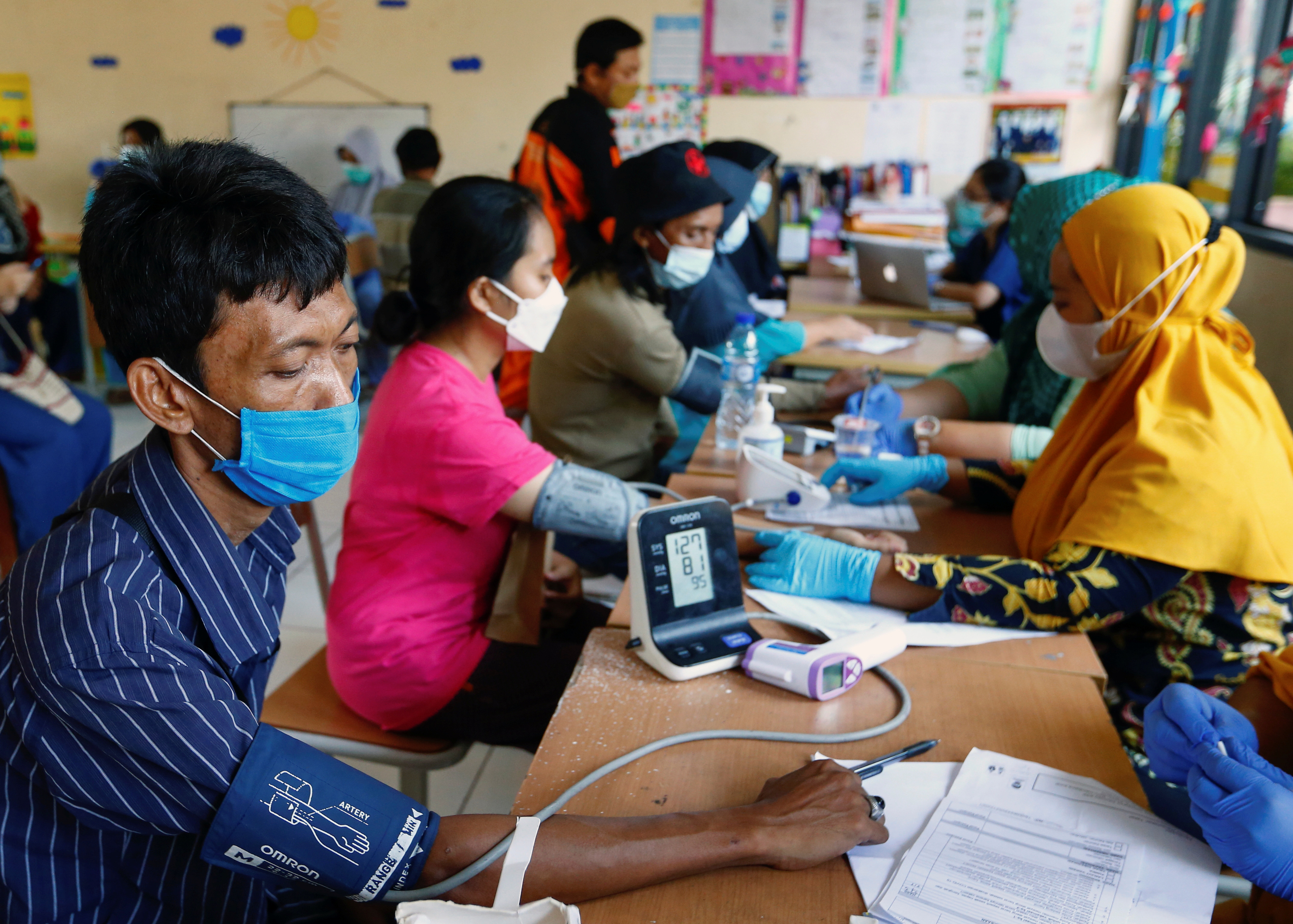 People wearing protective face masks undergo a health screening before receiving their dose of the AstraZeneca coronavirus disease (COVID-19) vaccine at a kindergarten in Jakarta, Indonesia, June 10, 2021. REUTERS/Ajeng Dinar Ulfiana