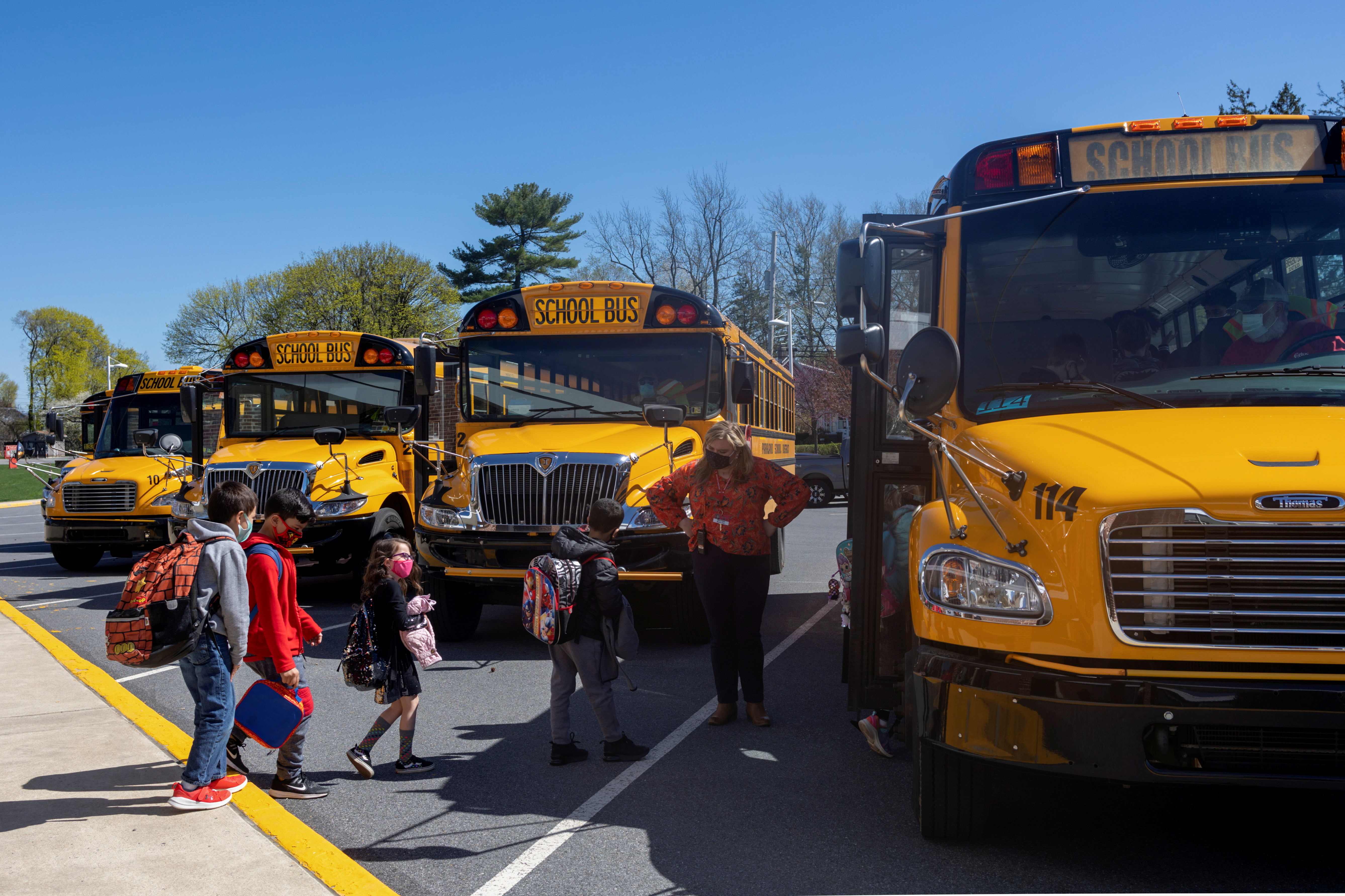 Students are led onto the bus after the school day ends at Kratzer Elementary School in Allentown, Pennsylvania, U.S., April 13, 2021.  REUTERS/Hannah Beier
