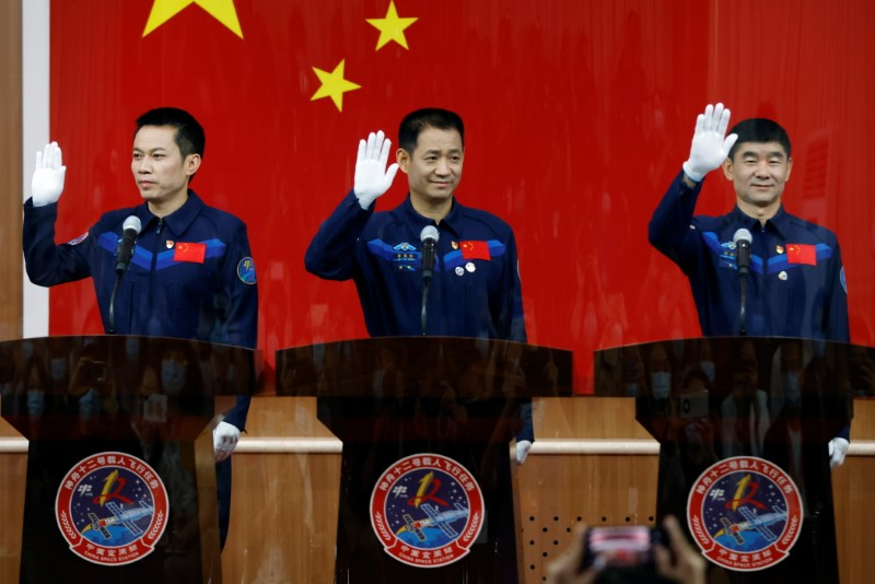 Chinese astronauts Nie Haisheng, Liu Boming, and Tang Hongbo wave as they meet members of the media behind a glass wall before the Shenzhou-12 mission to build China's space station, at Jiuquan Satellite Launch Center near Jiuquan, Gansu province, China June 16, 2021. REUTERS/Carlos Garcia Rawlins