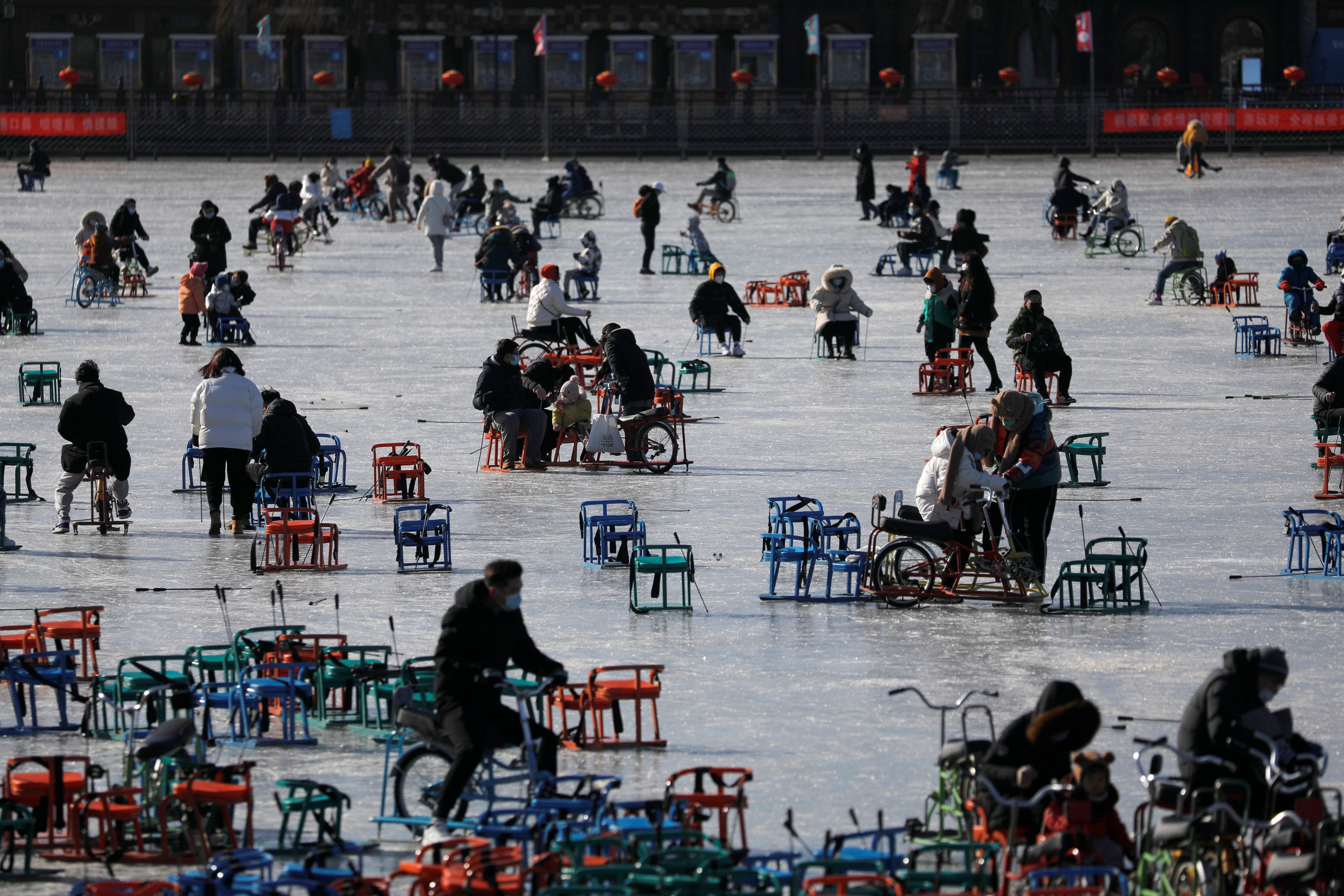 People wearing face masks following the coronavirus disease (COVID-19) outbreak skate on a frozen lake which has been turned to an ice rink, in Beijing, China, January 16, 2021. Picture taken January 16, 2021. REUTERS/Tingshu Wang
