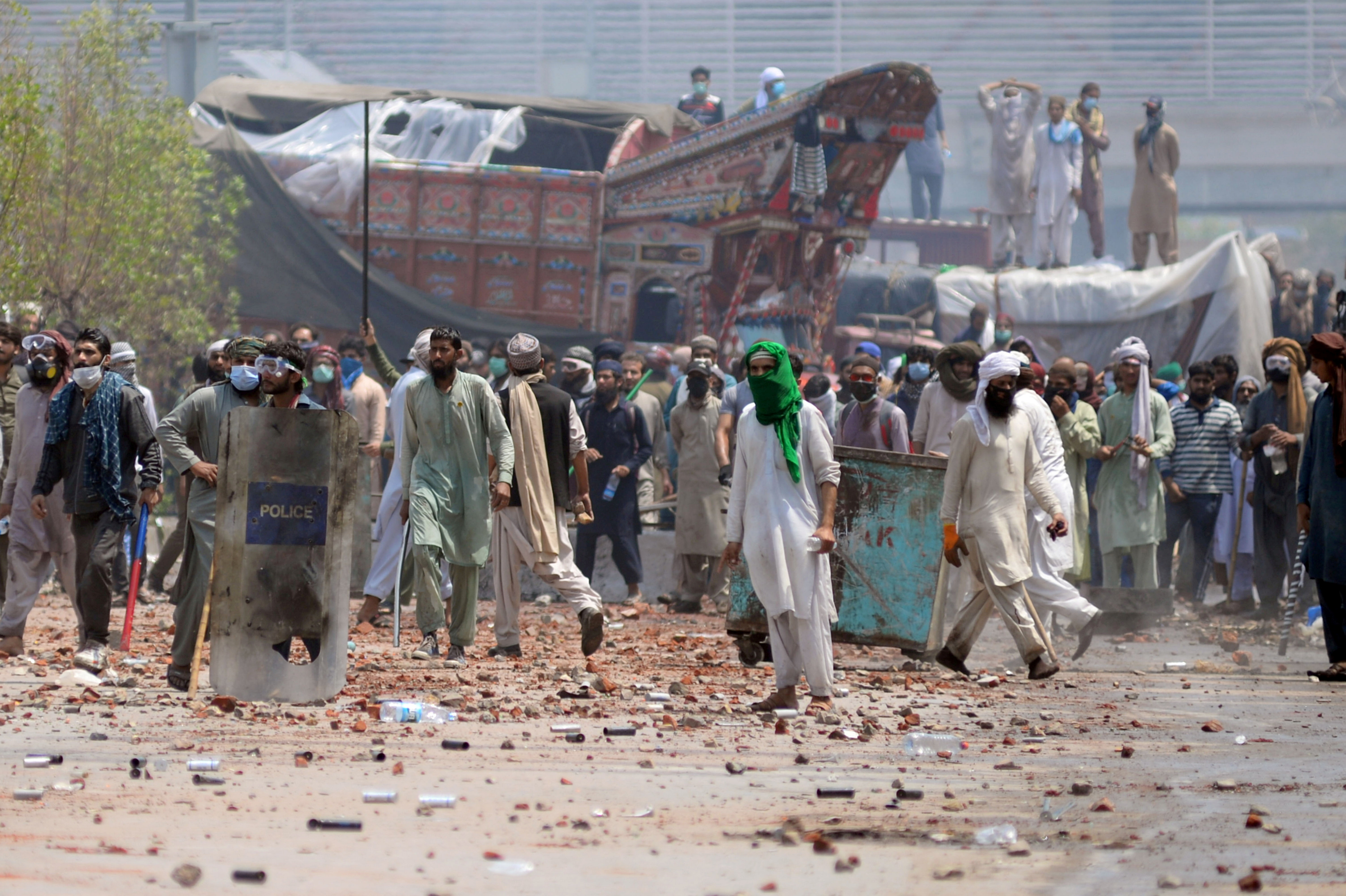 Supporters of the banned Islamist political party Tehrik-e-Labaik Pakistan (TLP) with sticks and stones block a road during a protest in Lahore, Pakistan April 18, 2021. REUTERS/Stringer/File Photo
