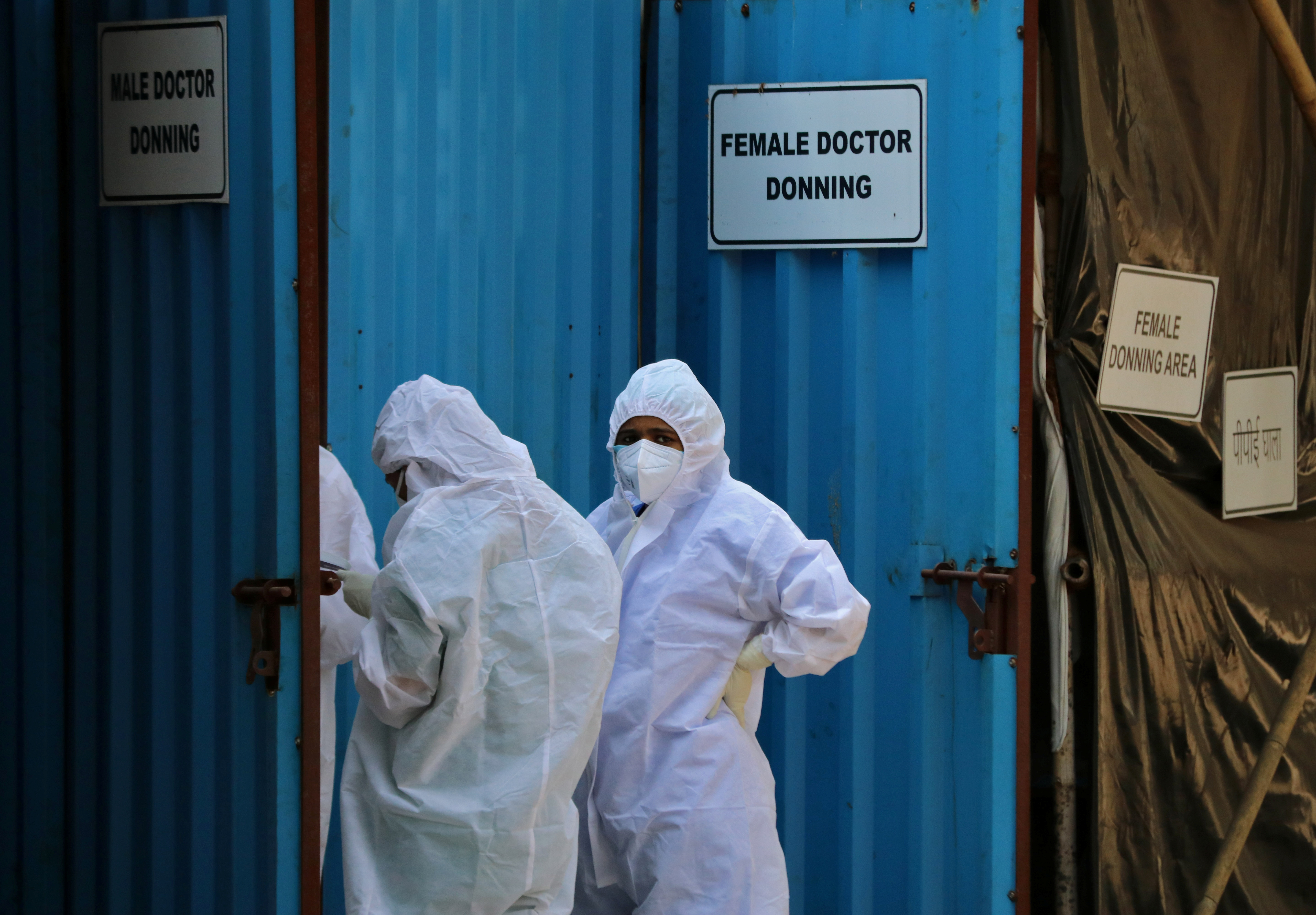 Healthcare workers wearing personal protective equipment (PPE) stand outside a donning area at a COVID-19 care facility, amidst the spread of the coronavirus disease (COVID-19) in Mumbai, India, May 4, 2021. REUTERS/Niharika Kulkarni