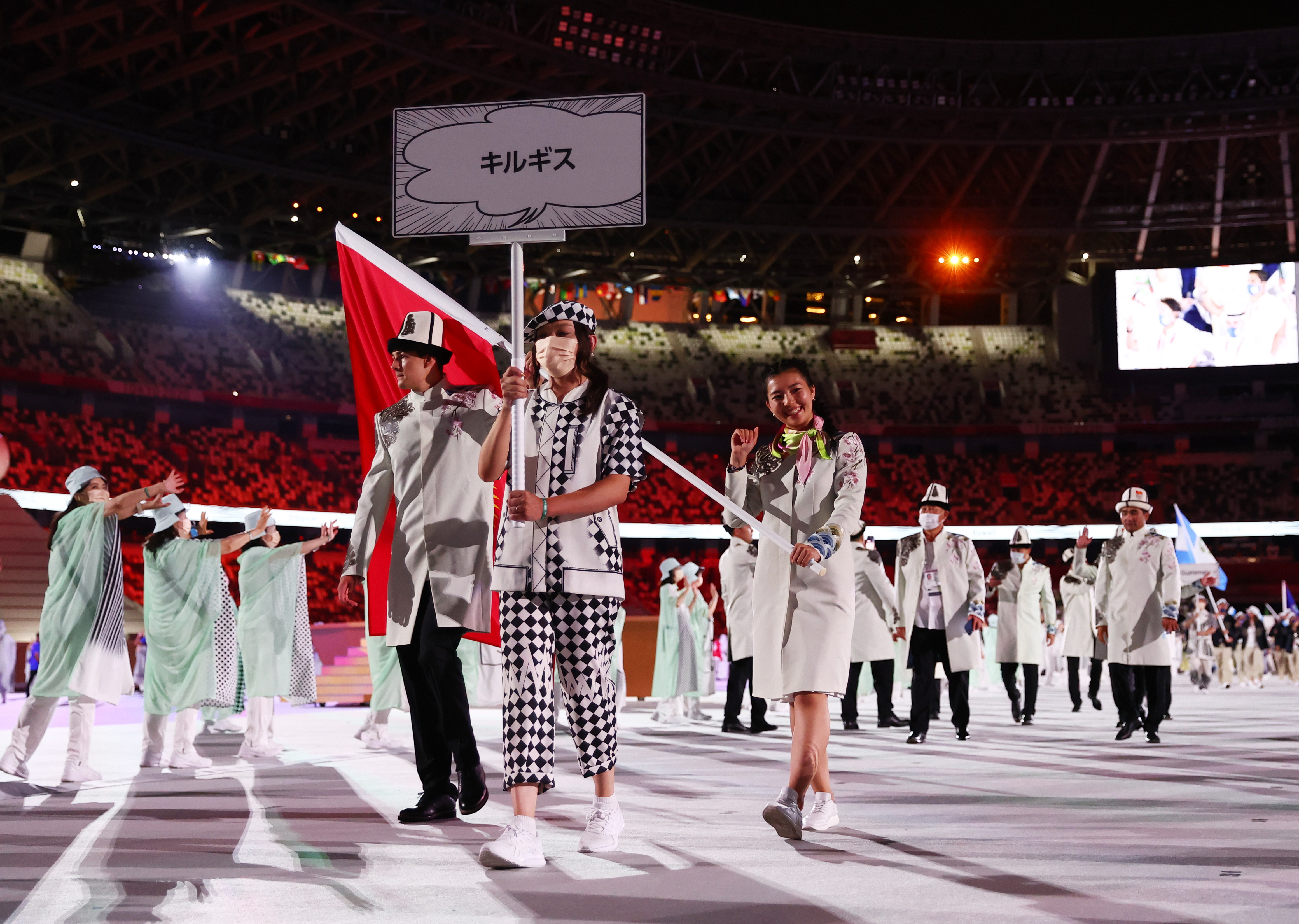 Tokyo 2020 Olympics - The Tokyo 2020 Olympics Opening Ceremony - Olympic Stadium, Tokyo, Japan - July 23, 2021. Flag bearers Kanykei Kubanychbekova of Kyrgyzstan and Denis Petrashov of Kyrgyzstan lead their contingent during the athletes' parade at the opening ceremony REUTERS/Kai Pfaffenbach
