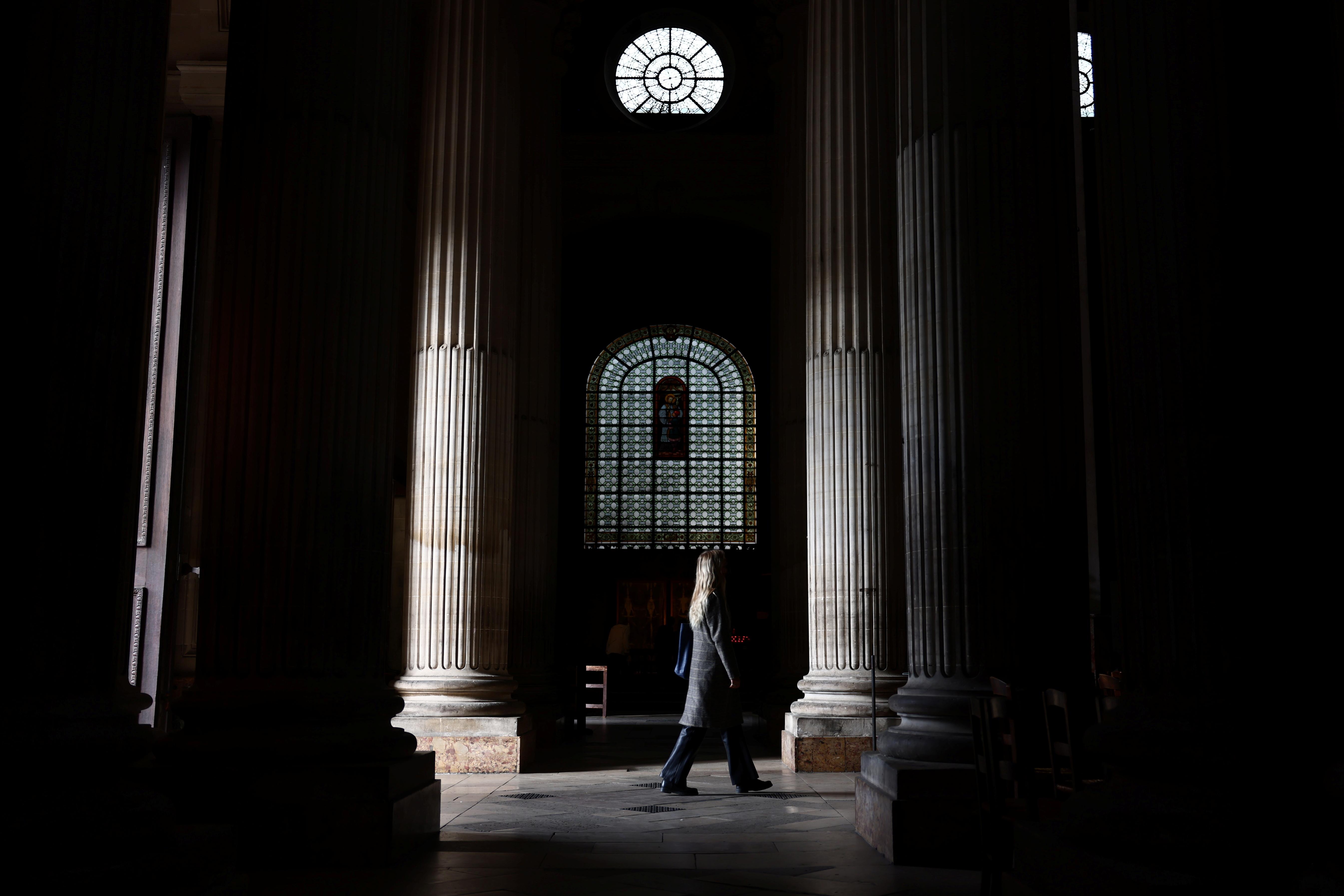 A woman walks into the Saint-Sulpice church in Paris, France, October 4, 2021. REUTERS/Sarah Meyssonnier