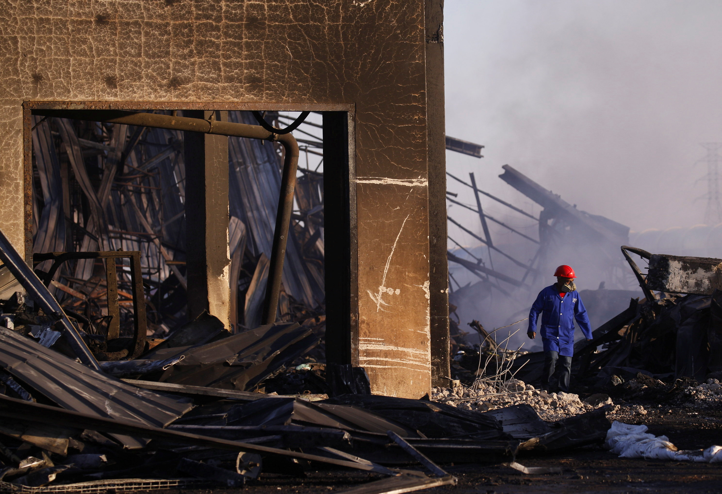 A man walks through the remnants of a warehouse which was burned during days of looting following the imprisonment of former South African President Jacob Zuma, in Durban, South Africa, July 17, 2021. REUTERS/Rogan Ward