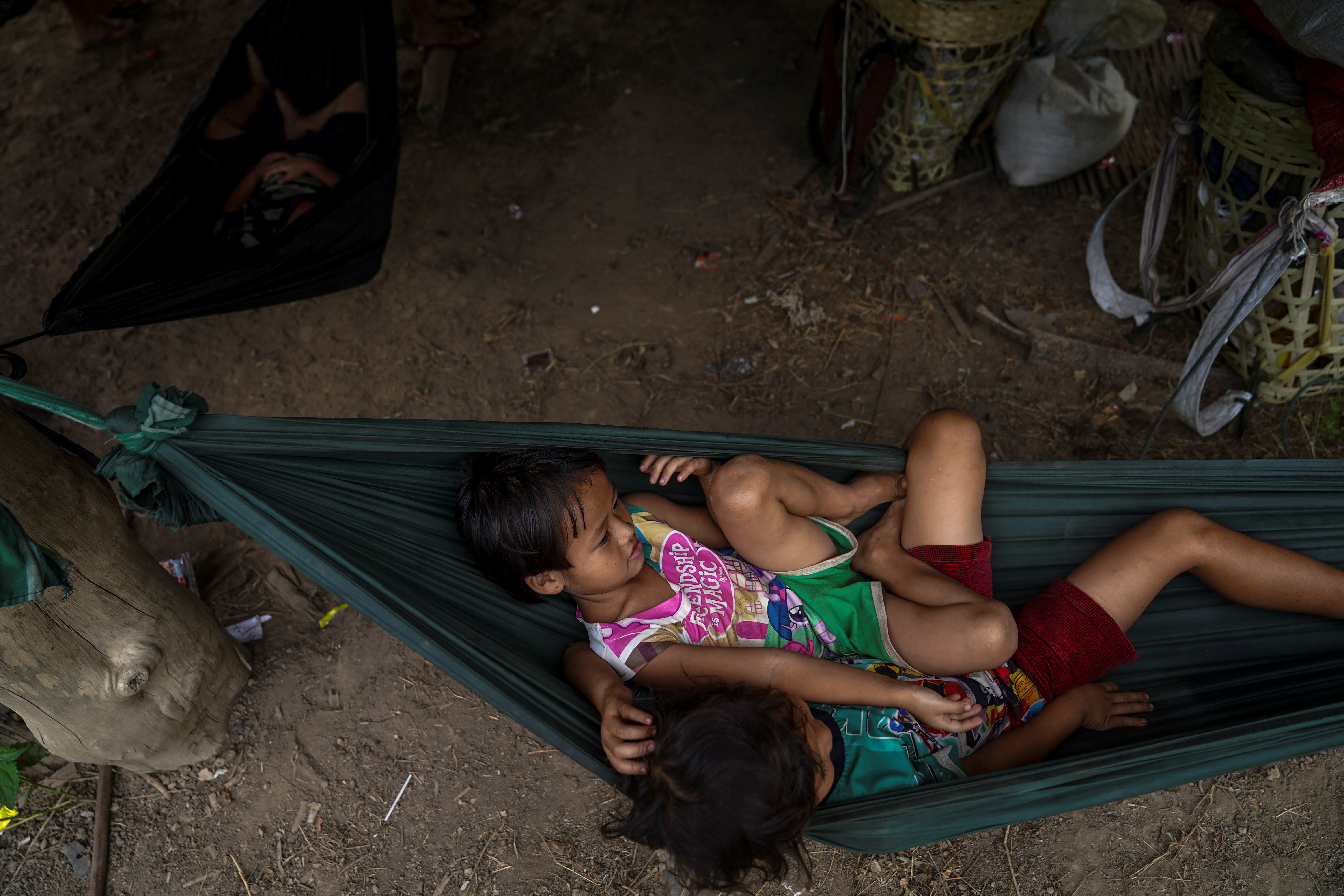 Children sit in a hammock near the Burmese border in Mae Hong Son province, Thailand, while fleeing from gunfire between ethnic minority Karen insurgents and Myanmar military, April 29, 2021. REUTERS/Athit Perawongmetha