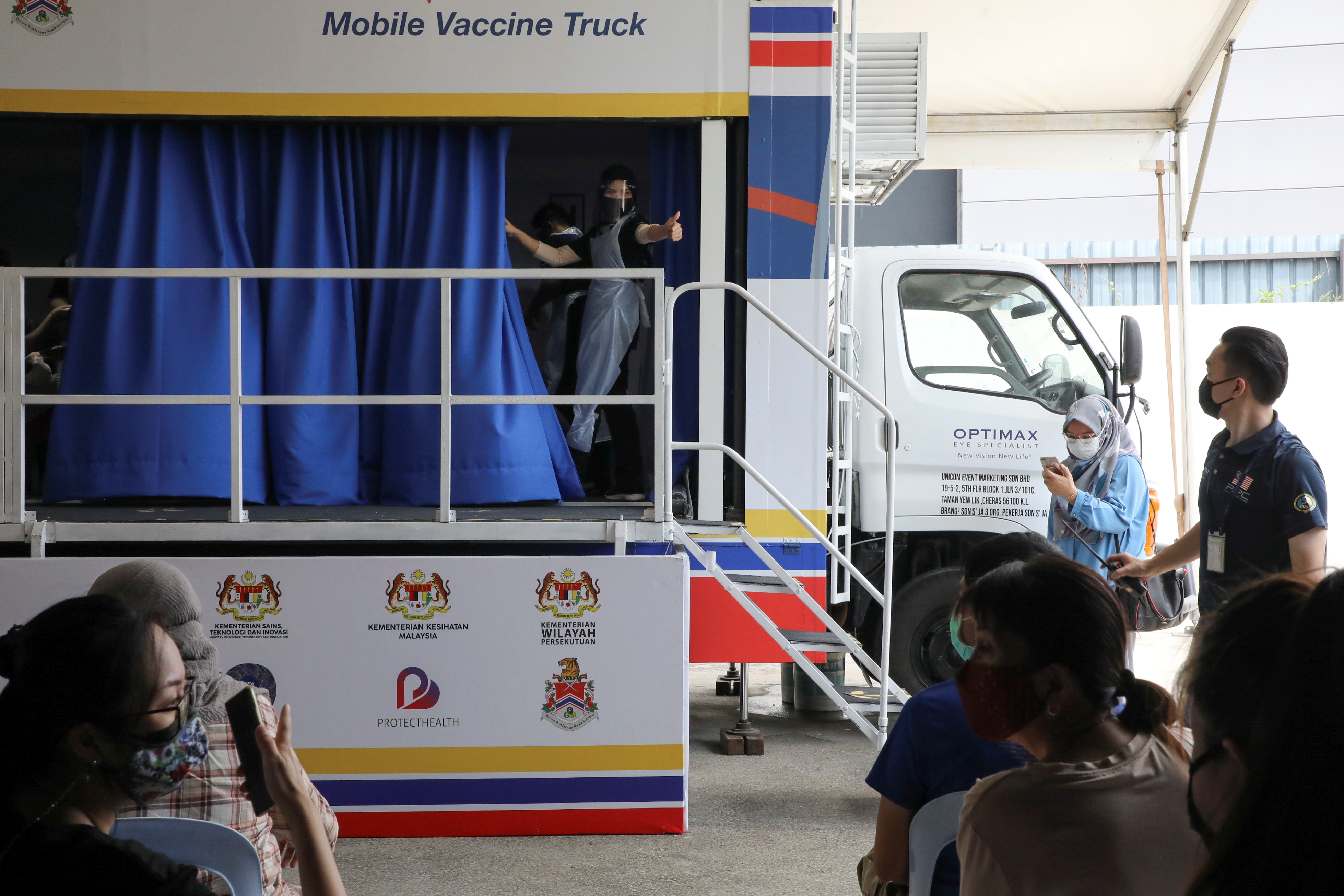 A medical worker gestures inside a coronavirus disease (COVID-19) vaccination truck in Kuala Lumpur, Malaysia June 8, 2021. REUTERS/Lim Huey Teng