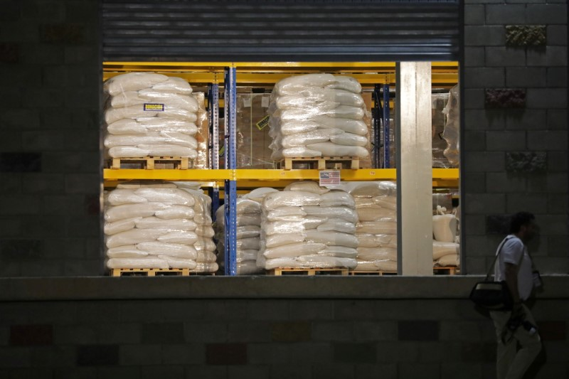 A man walks past aid at a warehouse where international humanitarian aid for Venezuela is being stored, during a visit by U.S. Secretary of State Mike Pompeo and Colombia's President Ivan Duque, near the La Unidad cross-border bridge between Colombia and Venezuela in Cucuta, Colombia April 14, 2019. REUTERS/Luisa Gonzalez/File Photo