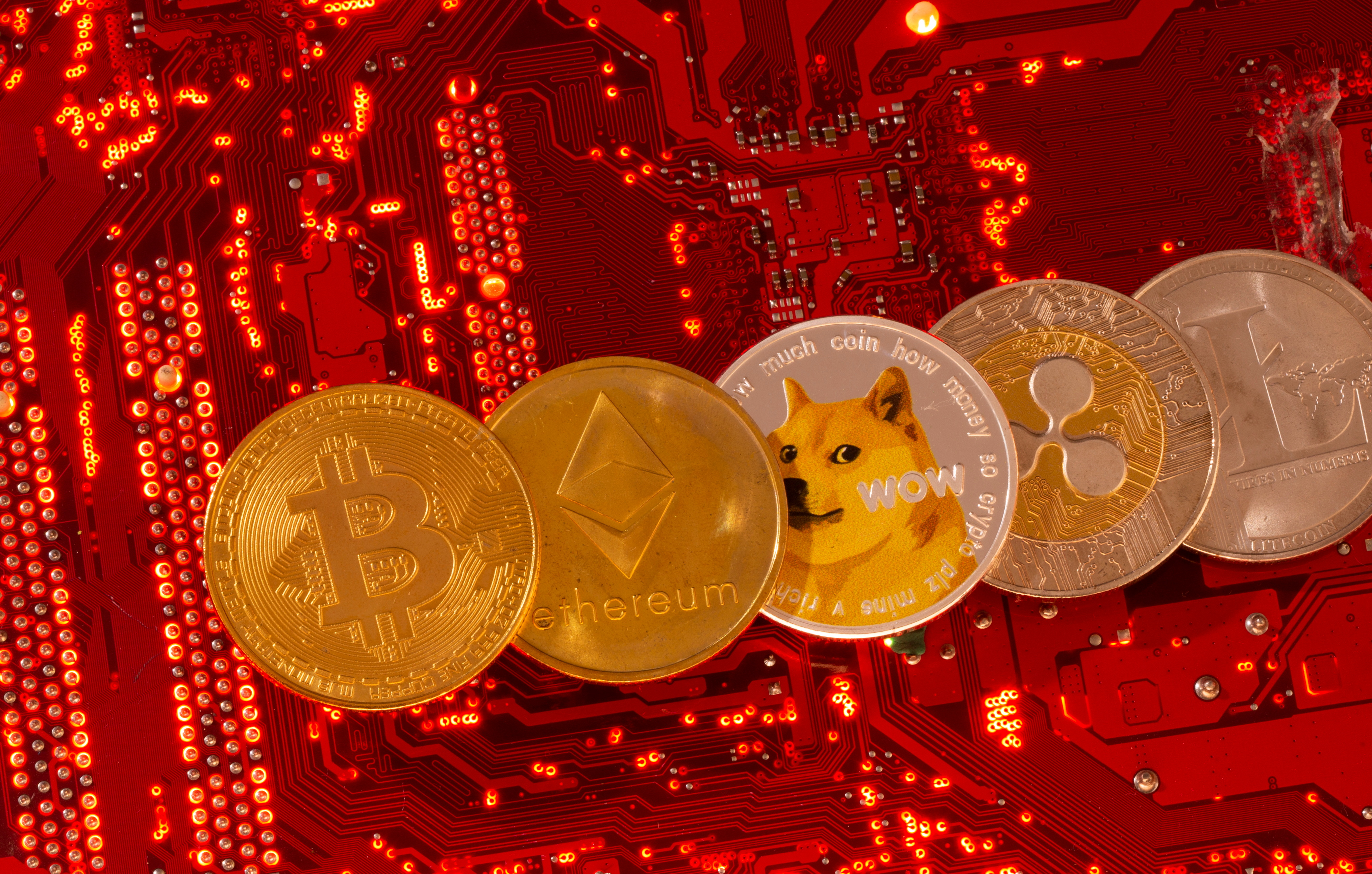 Representations of cryptocurrencies Bitcoin, Ethereum, DogeCoin, Ripple, Litecoin are placed on PC motherboard in this illustration taken June 29, 2021. REUTERS/Dado Ruvic/Illustration