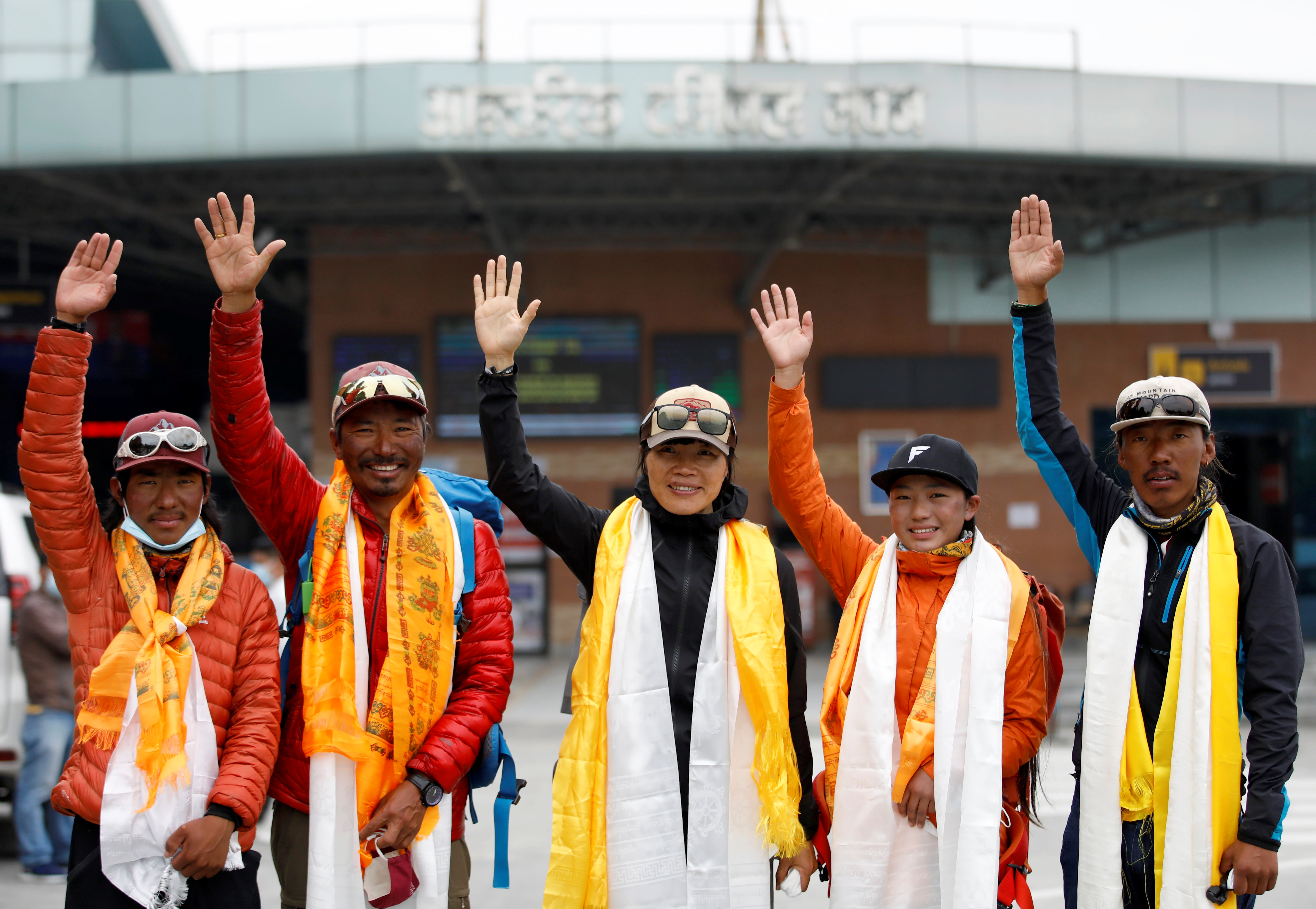Hong Kong's Tsang Yin-Hung, 45, (C), who scaled Mount Everest in less than 26 hours, the shortest time taken by any woman after starting from the base camp, waves for a picture along with her team members, upon her arrival after climbing Everest, in Kathmandu, Nepal May 30, 2021. REUTERS/Navesh Chitrakar